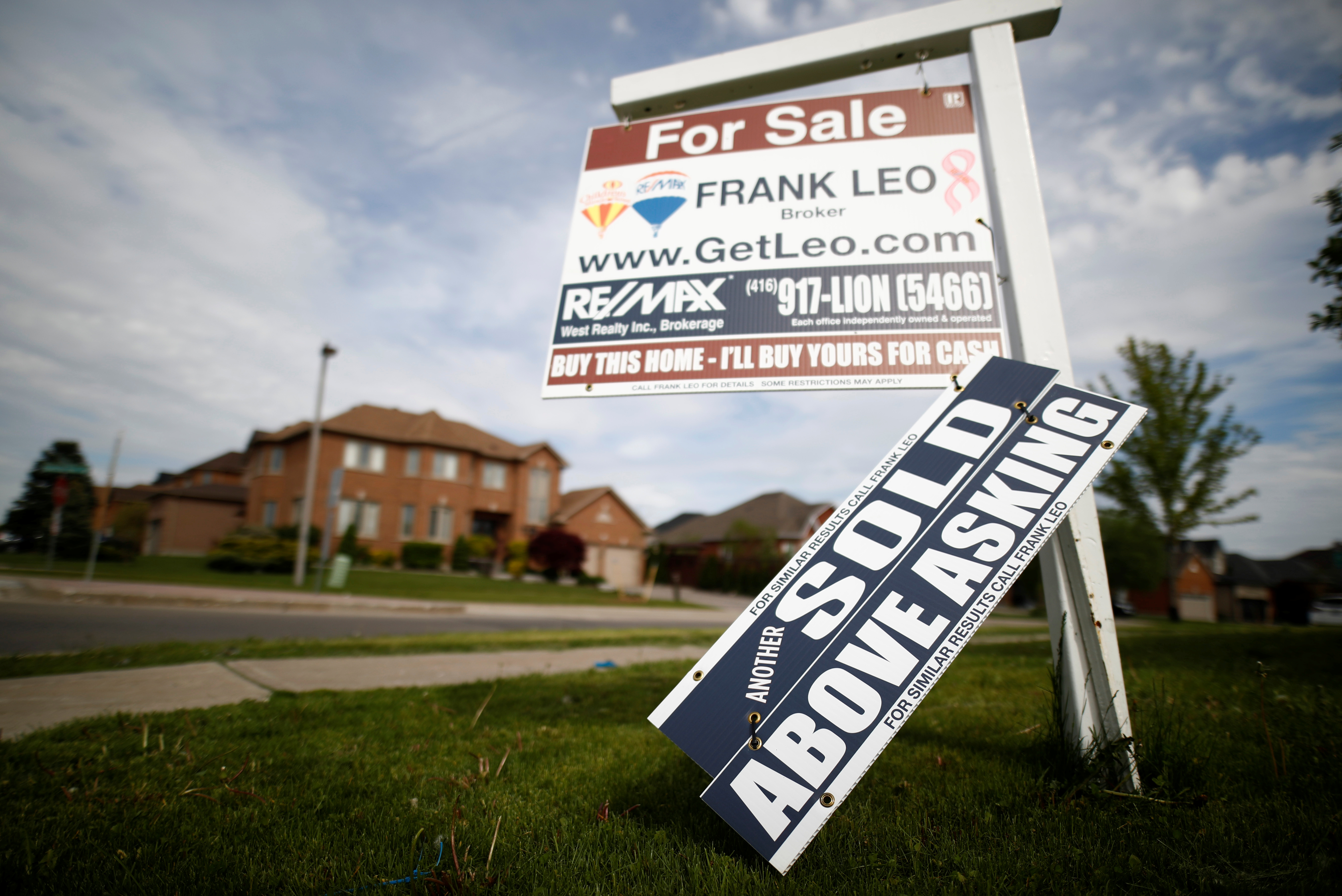 "A real estate sign that reads ""For Sale"" and ""Sold Above Asking"" stands in front of housing in Toronto"