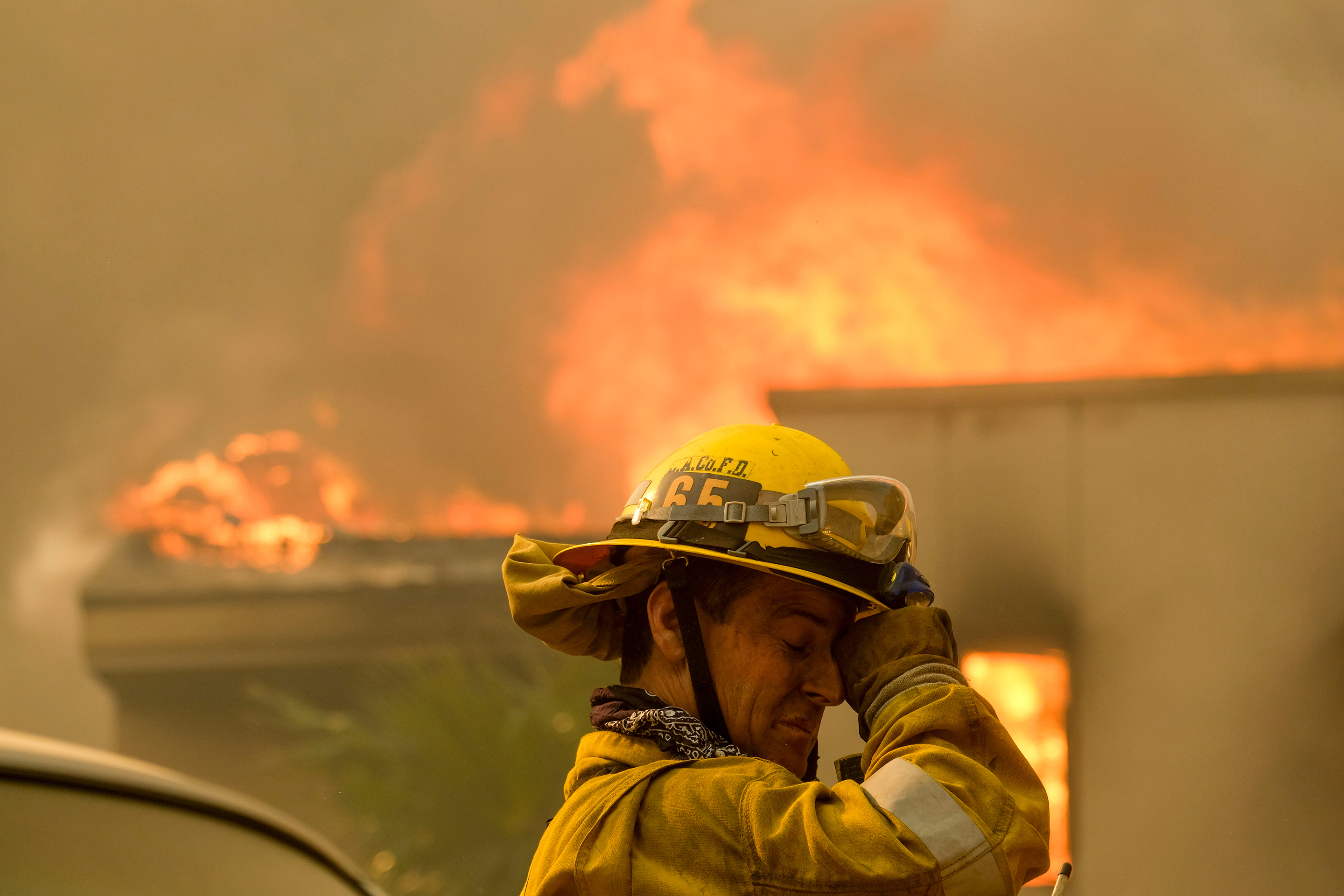 A firefighter keeps watch as the wildfire burns a home near Malibu Lake in Malibu, Calif.