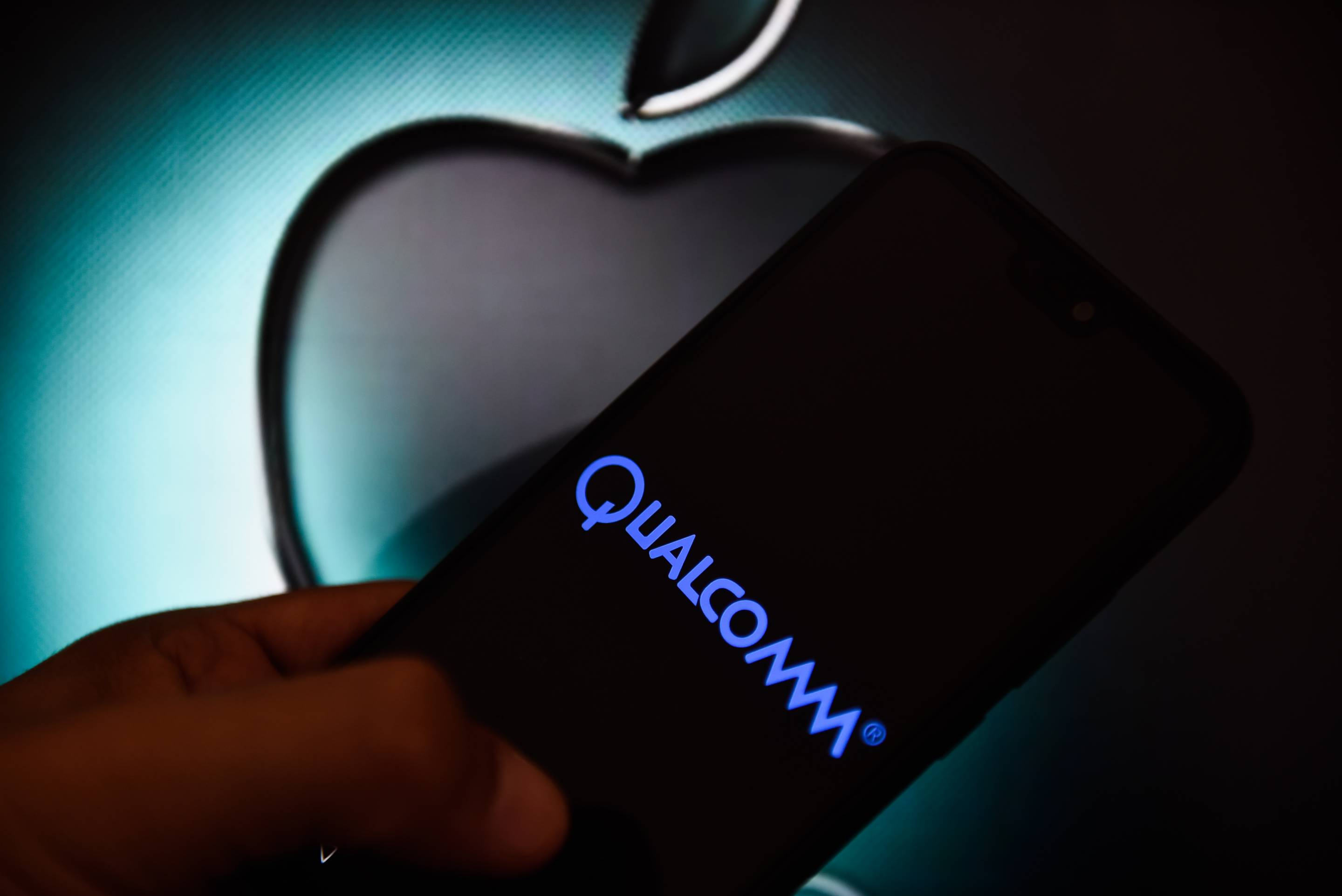 In this photo illustration a Qualcomm logo seen displayed on