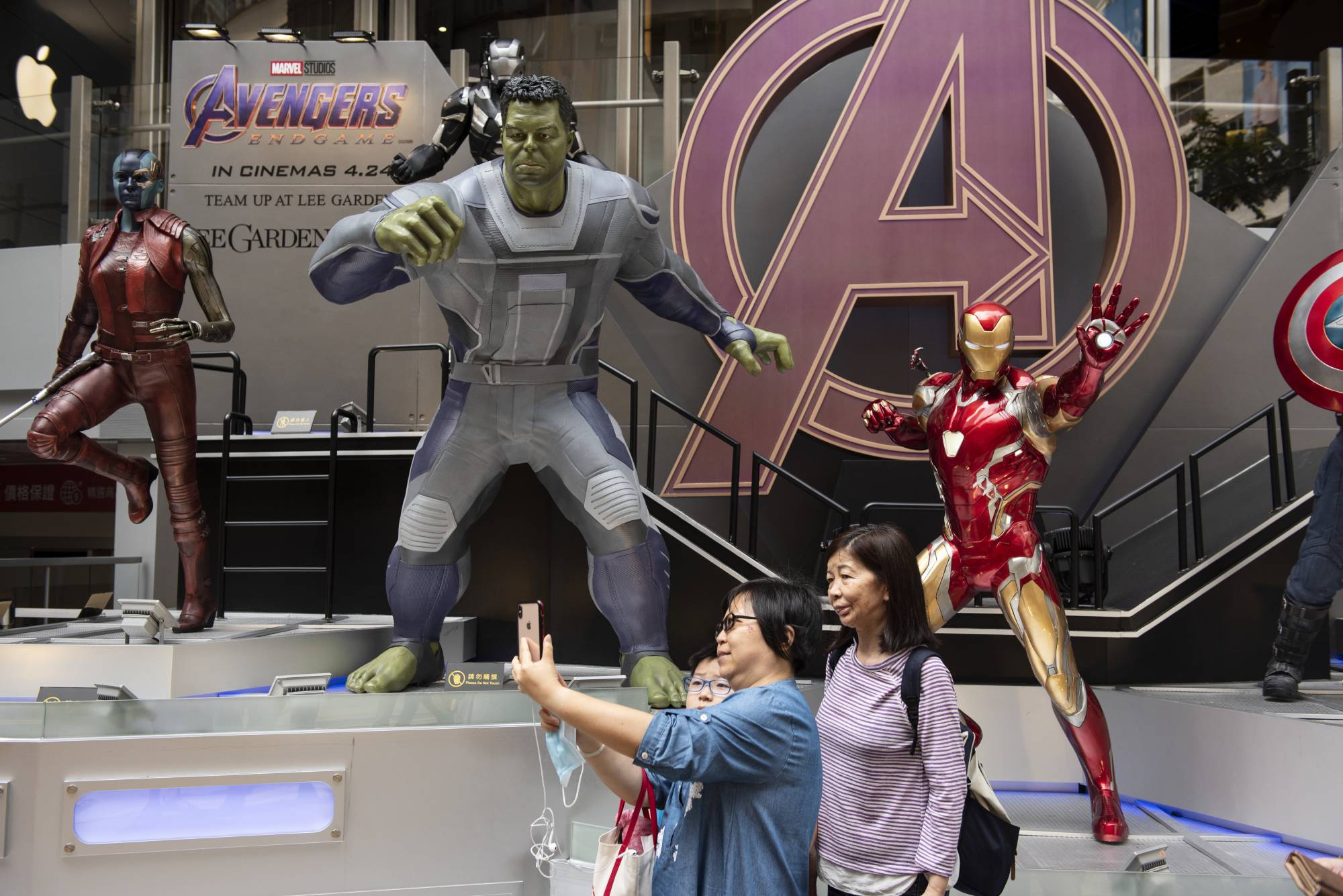 Pedestrians are seen taking a selfie with Marvel and Marvel