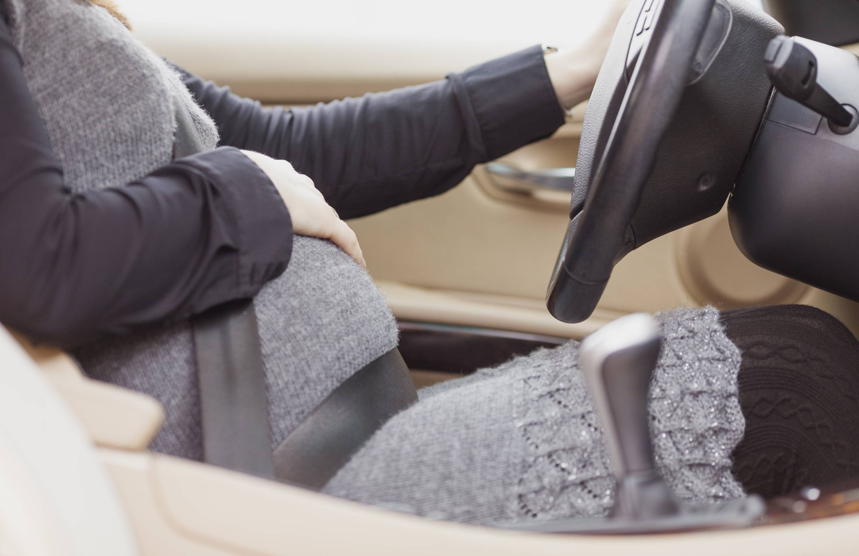 Pregnant woman driving a car with one hand