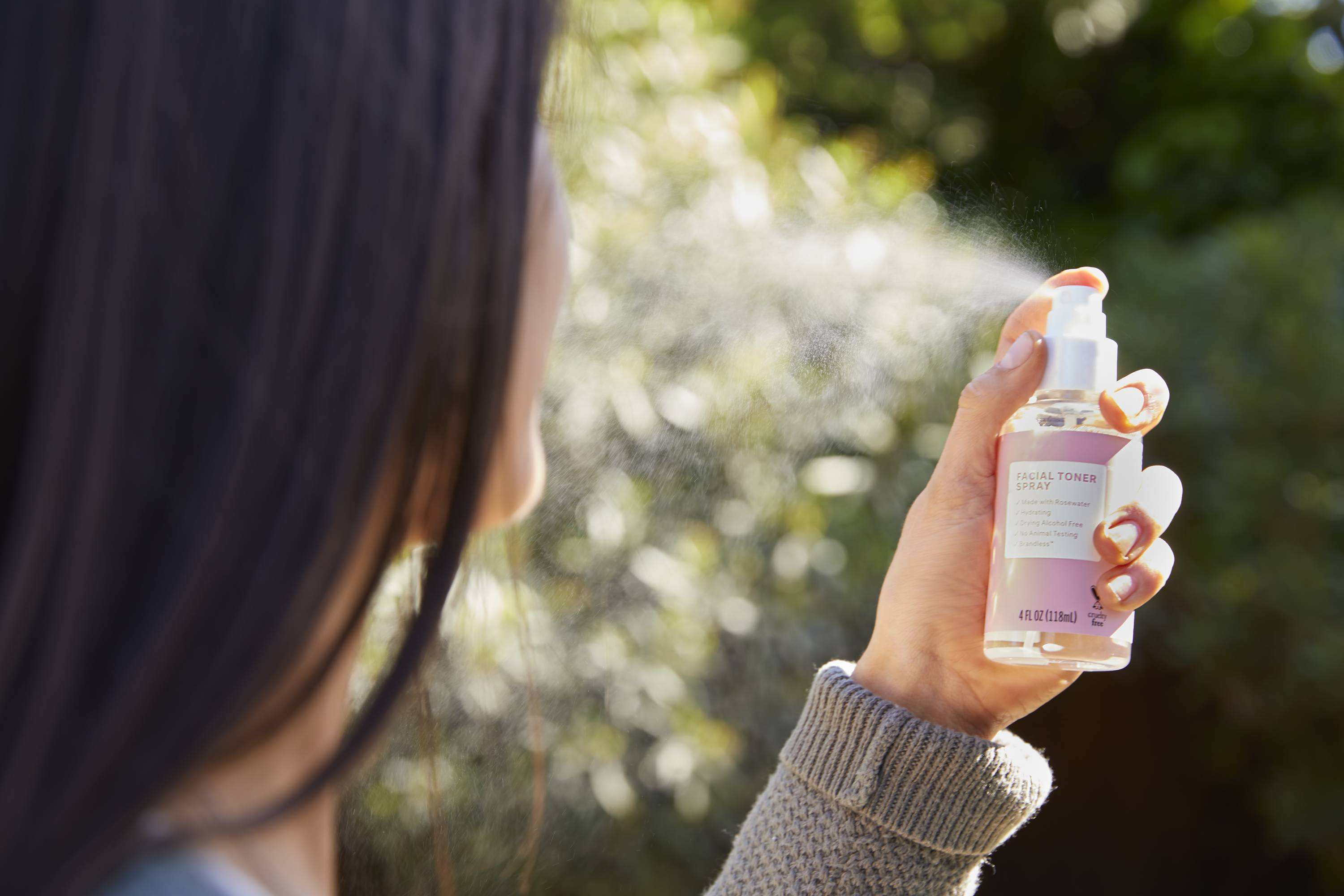 A woman holding the new Hydrating Rosewater Facial Toner Spray from D2C household goods company Brandless.