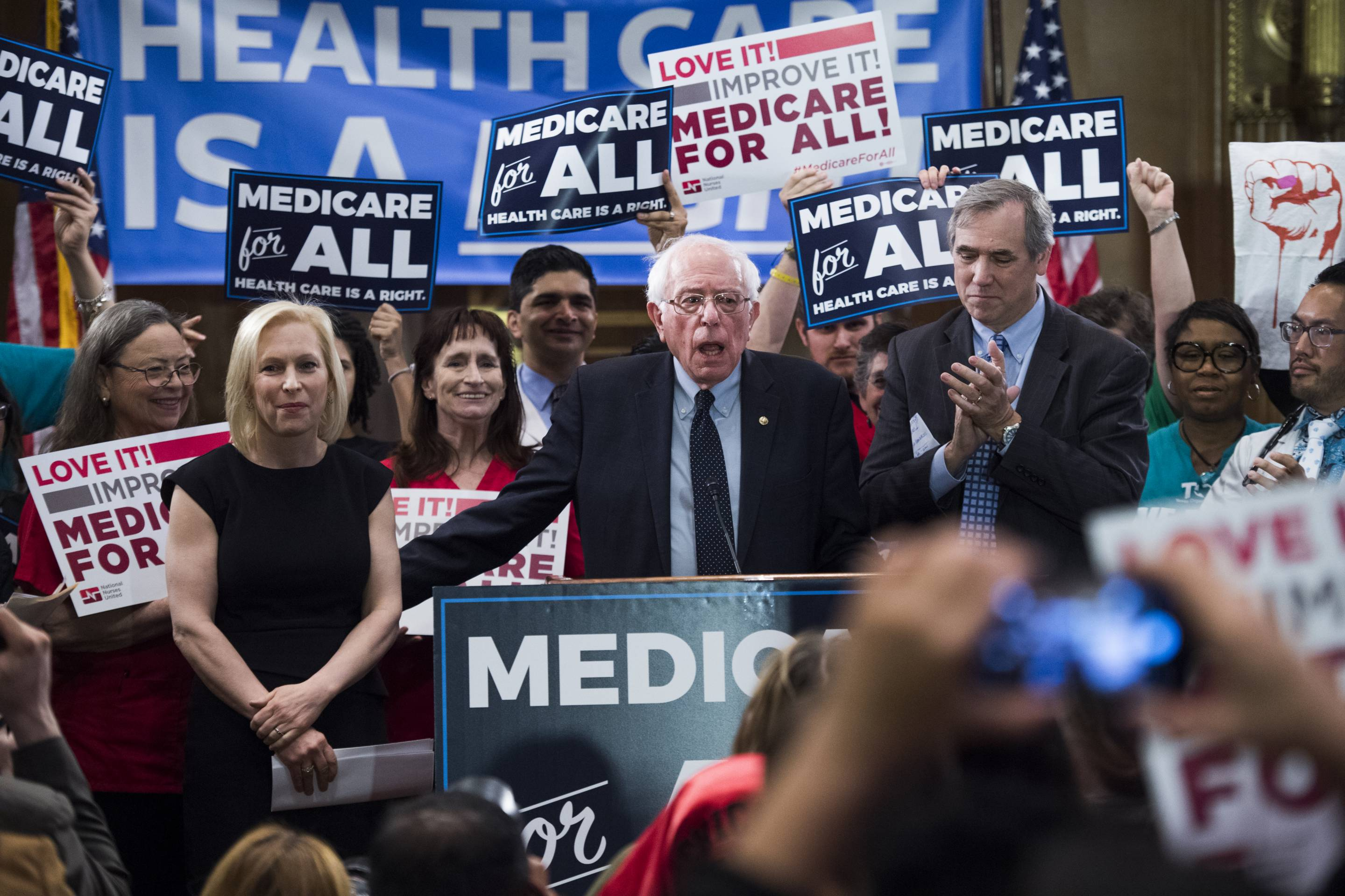 "From left, Senators Kirsten Gillibrand (D-N.Y.), Bernie Sanders (I-Vt.), and Jeff Merkley (D-Ore.), introduce the ""Medicare for All Act of 2019"" on Apr. 10."