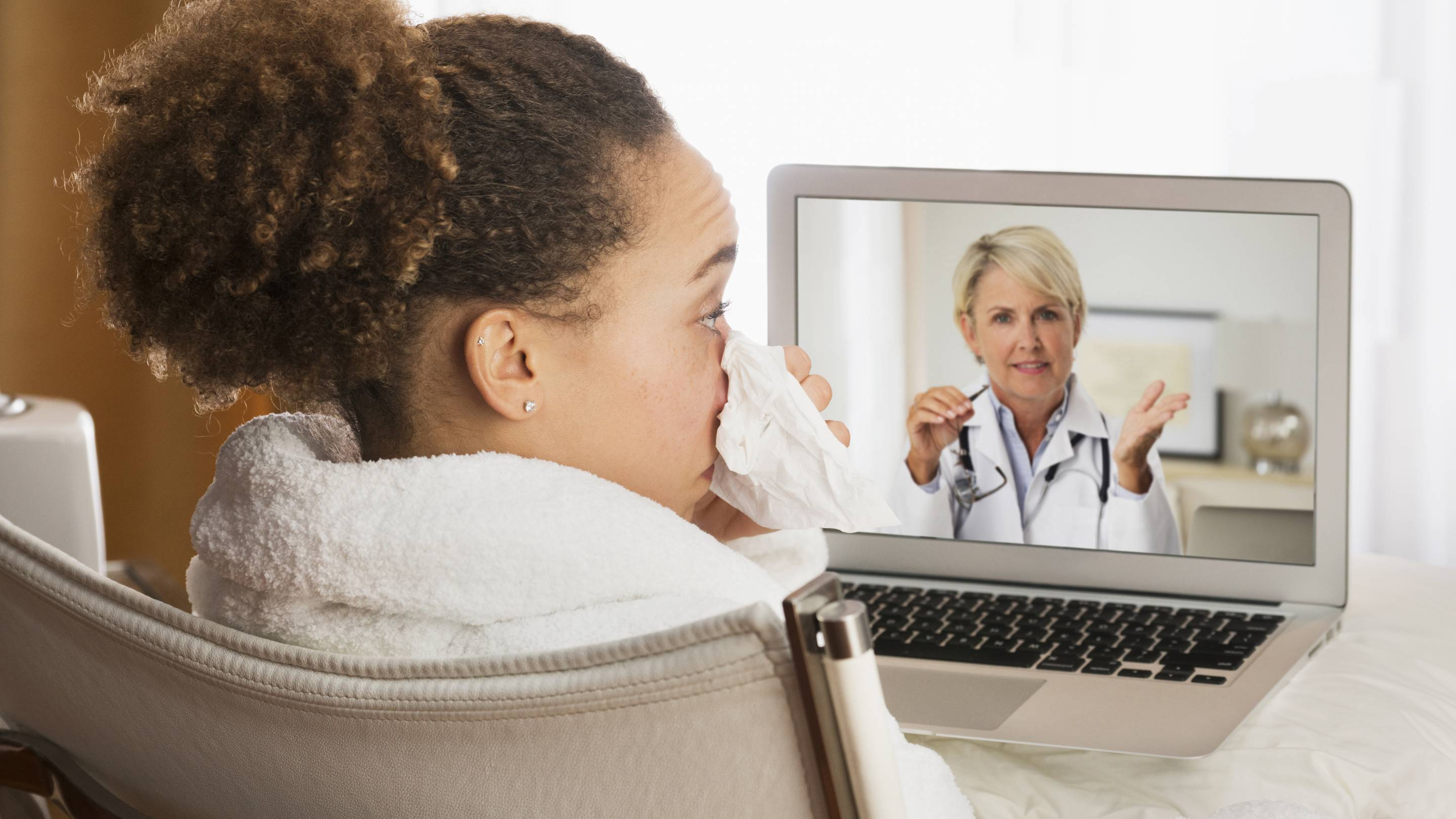 A sick woman video chats with her doctor on her laptop.