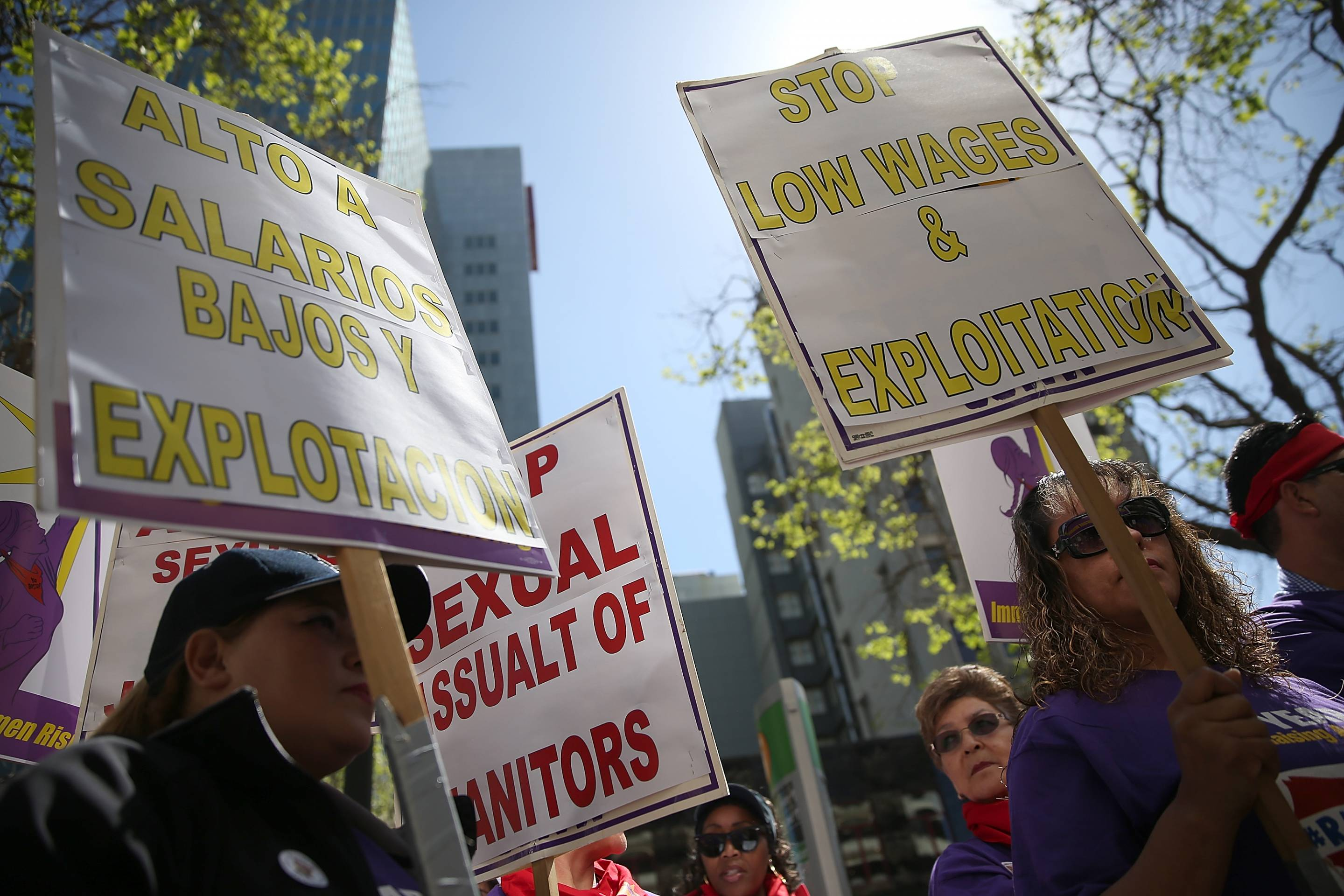 Union workers hold signs during a demonstration in support of a proposal to raise the California minimum wage to $15 by 2022 on March 31, 2016, in Oakland, Calif.