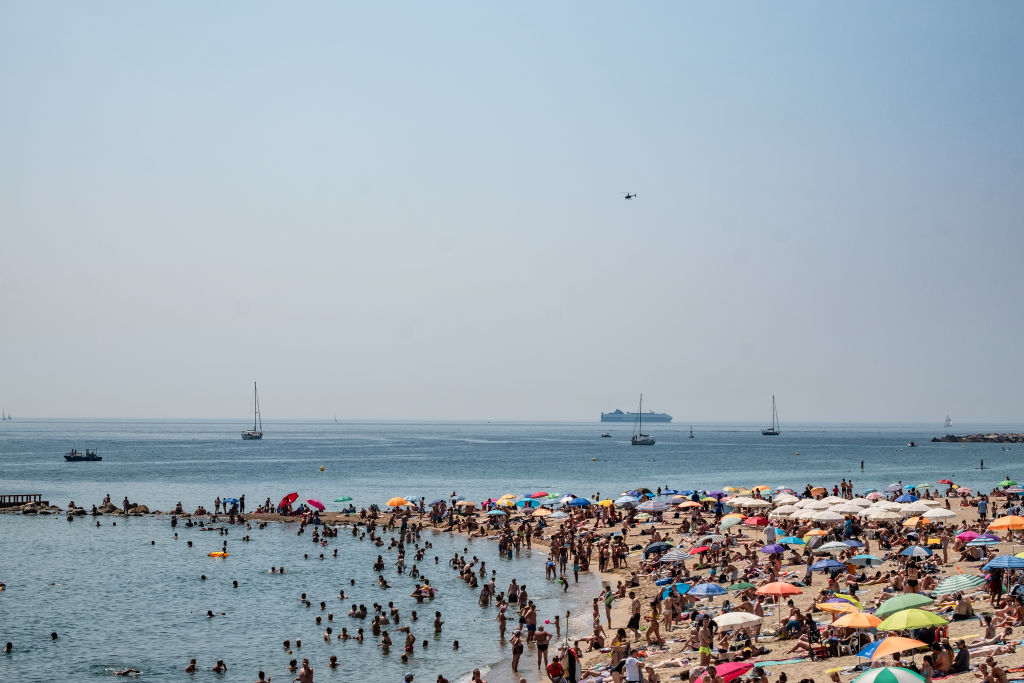 A crowd of people is seen on one of the beaches during a