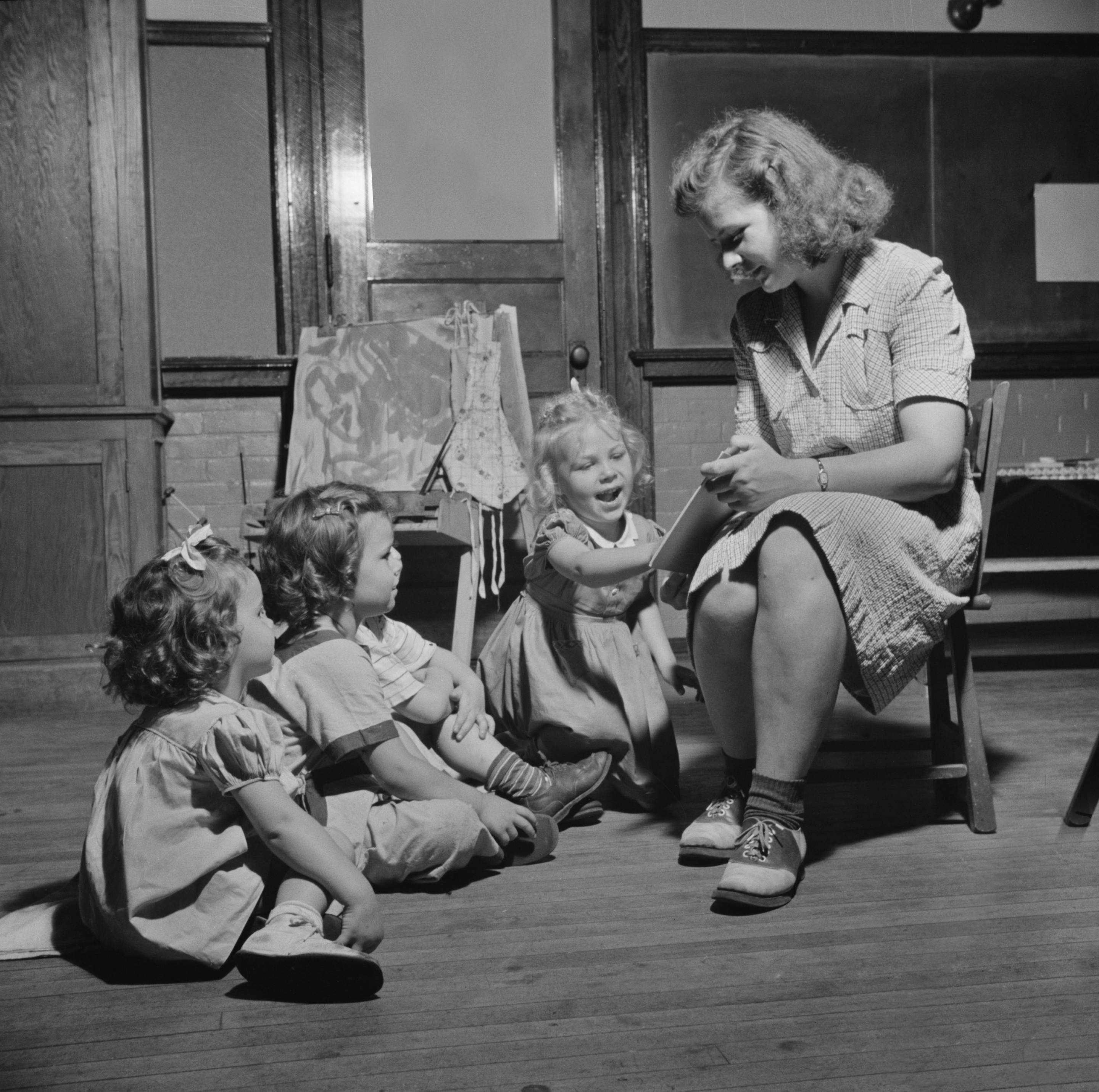 Woman Reading Story to Three Young Children at Child Care Center, New Britain, Connecticut, June 1943
