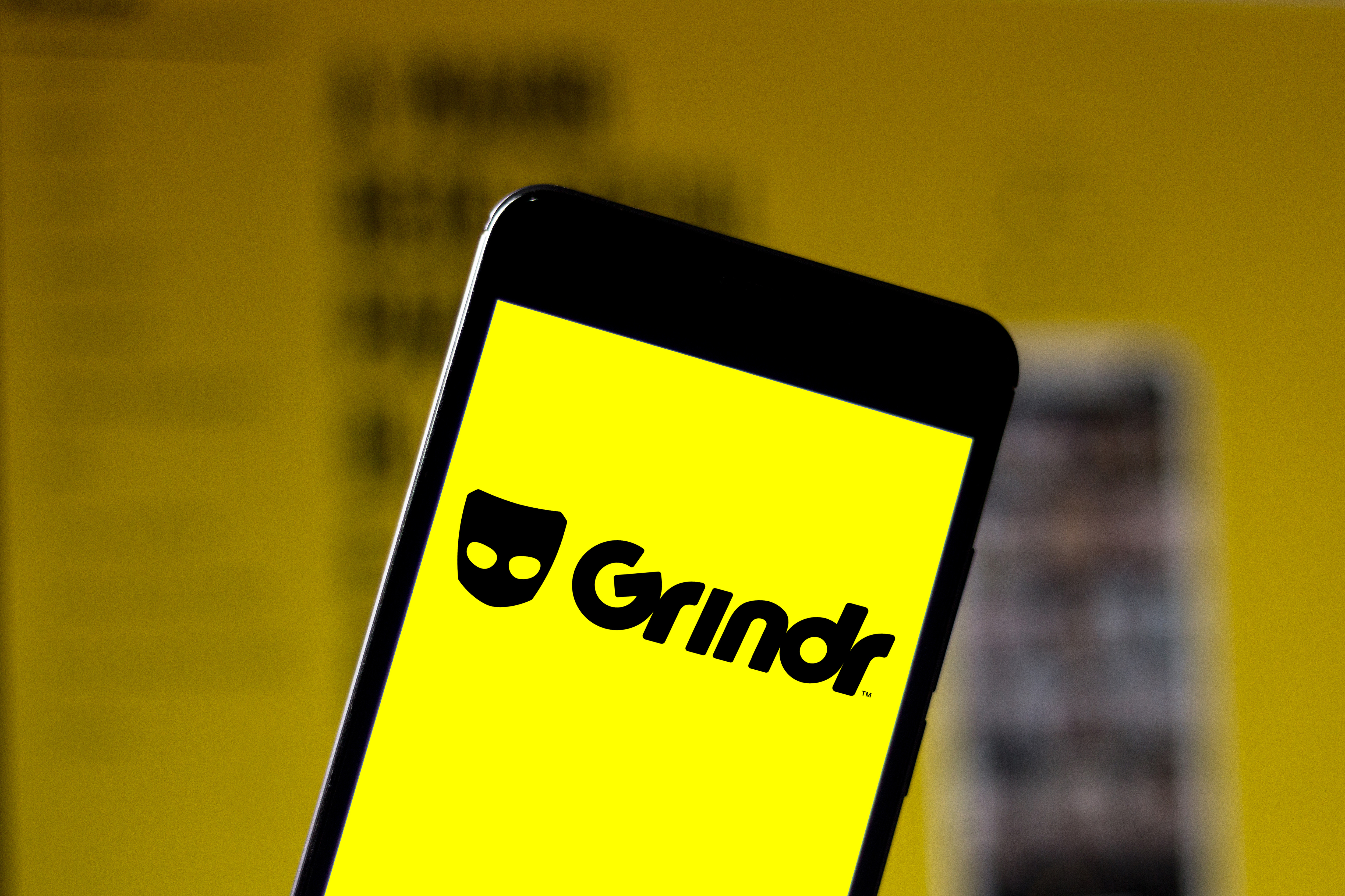 In this photo illustration a Grindr logo seen displayed on a