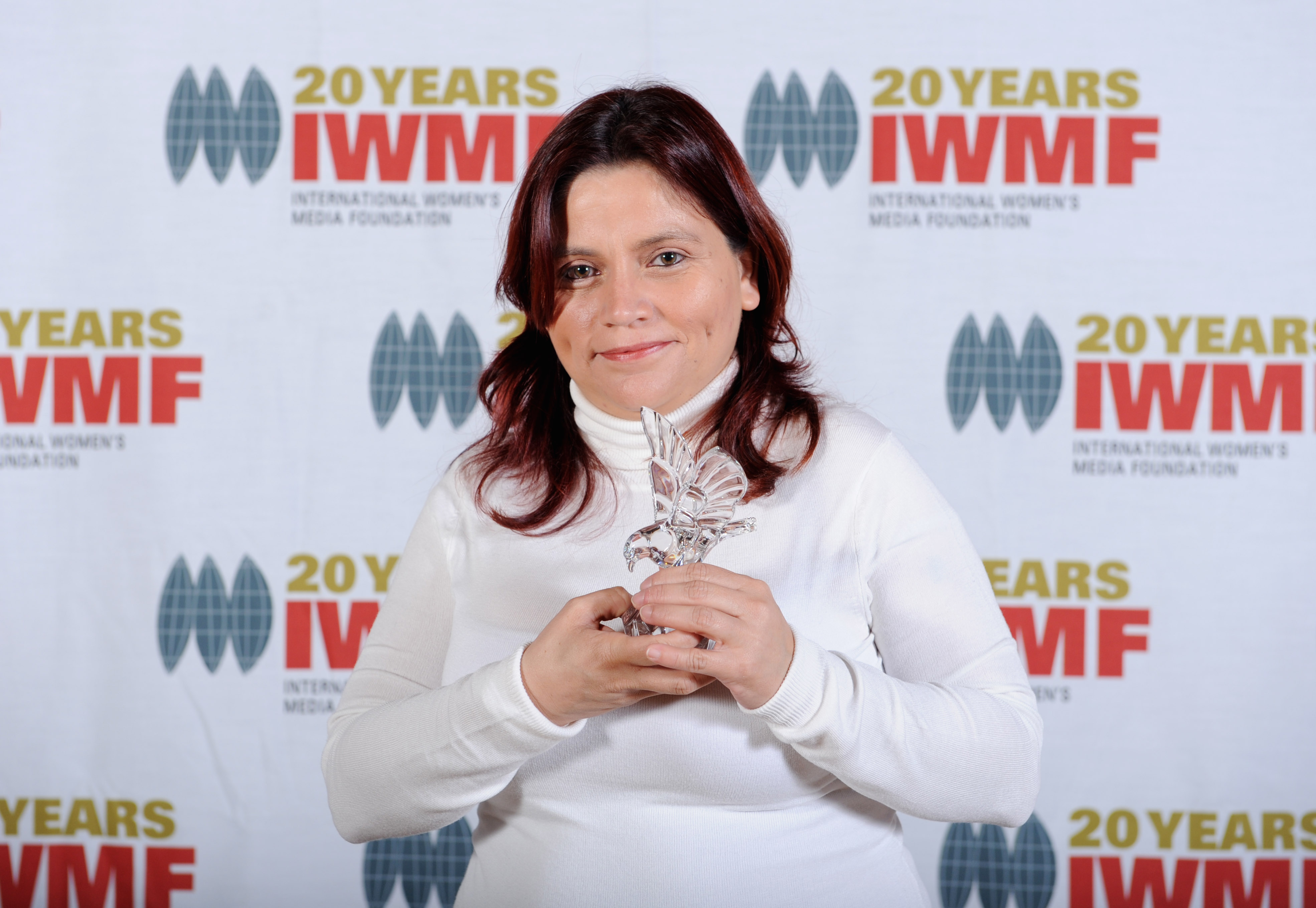 Colombian investigative reporter Claudia Duque holds her 2010 Courage in Journalism Award at the International Women's Media Foundation lunch in 2010. Duque faced torture by security service officials who, despite being convicted, remain free to this day.