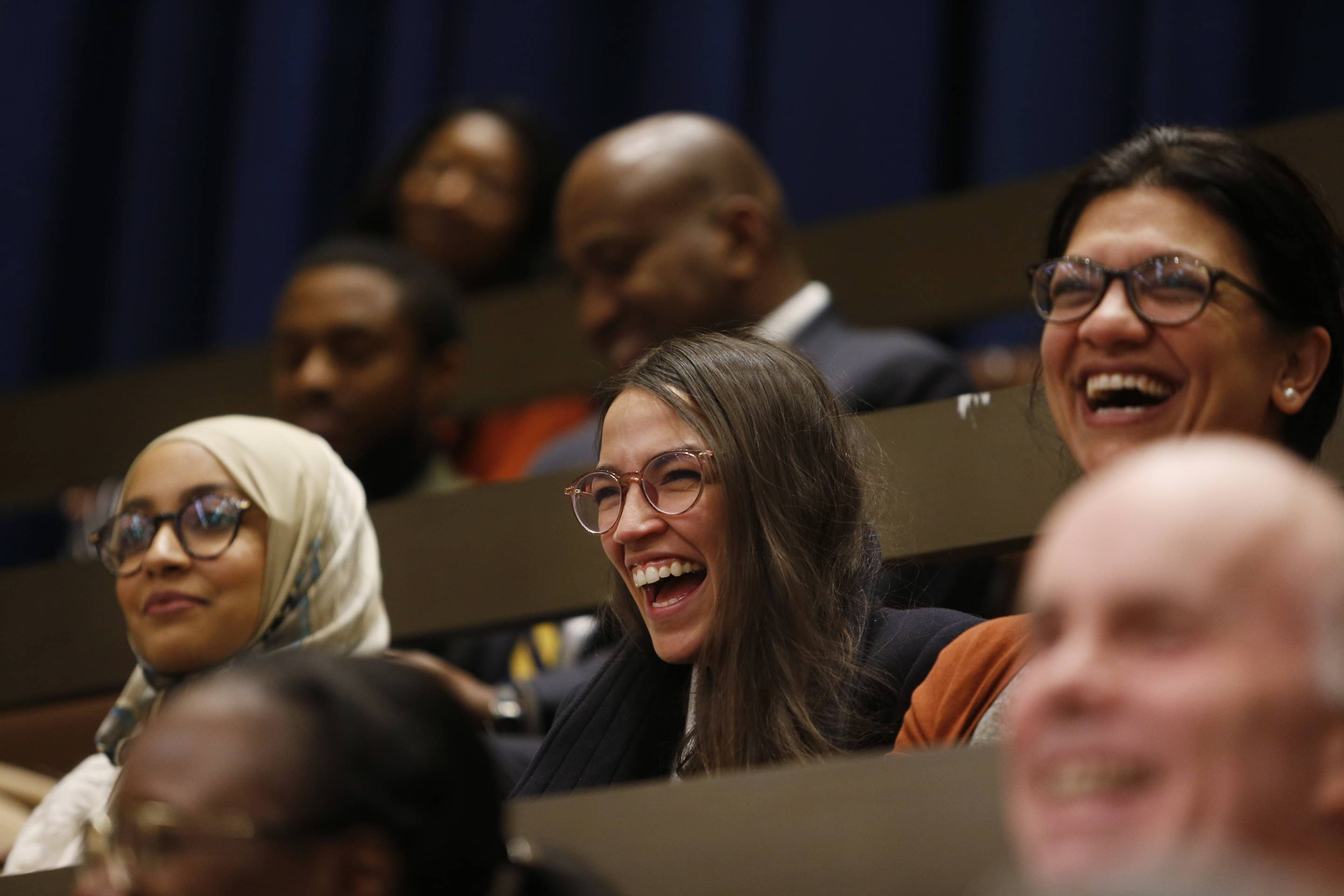 Alexandria Ocasio-Cortez and Rashida Tlaib laugh at a Boston City Council meeting on Dec. 5, 2018.