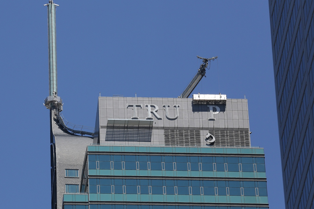 "Workers remove letters from the ""TRUMP"" sign on top of the Trump International Hotel and Tower in Toronto"