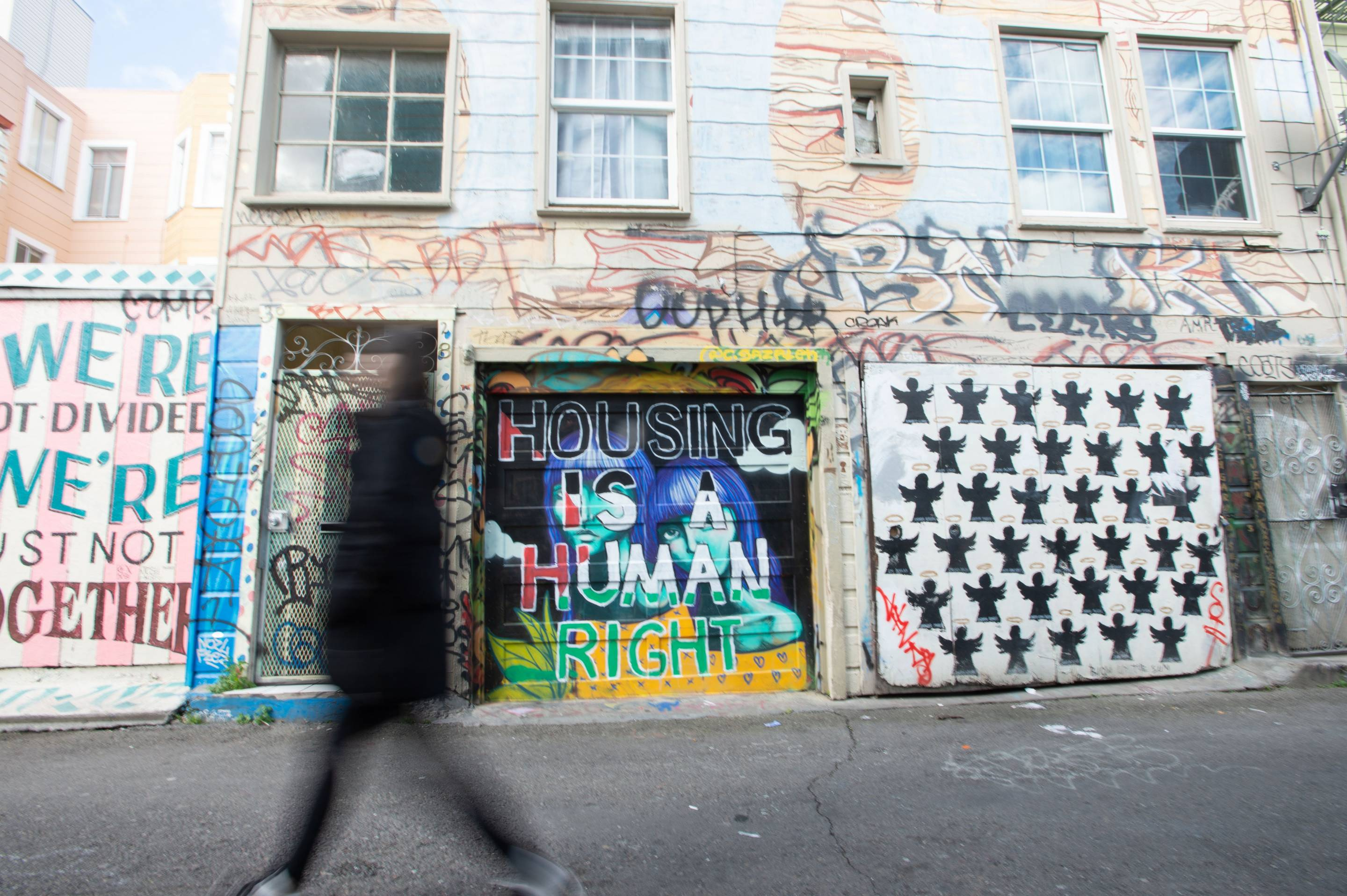 A woman walks by a housing-related mural in San Francisco on Feb. 6, 2019.
