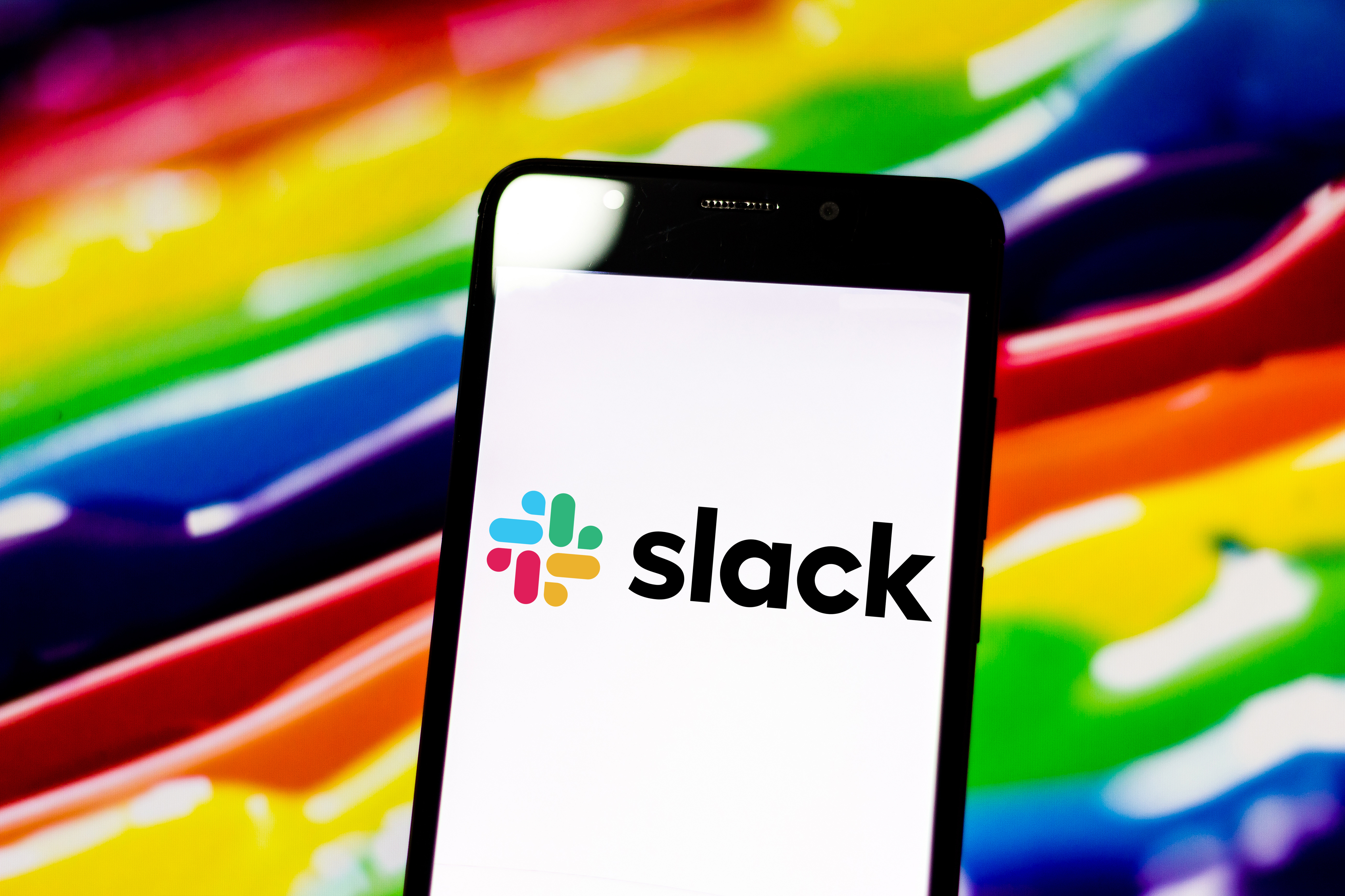 In this photo illustration the Slack logo seen displayed on