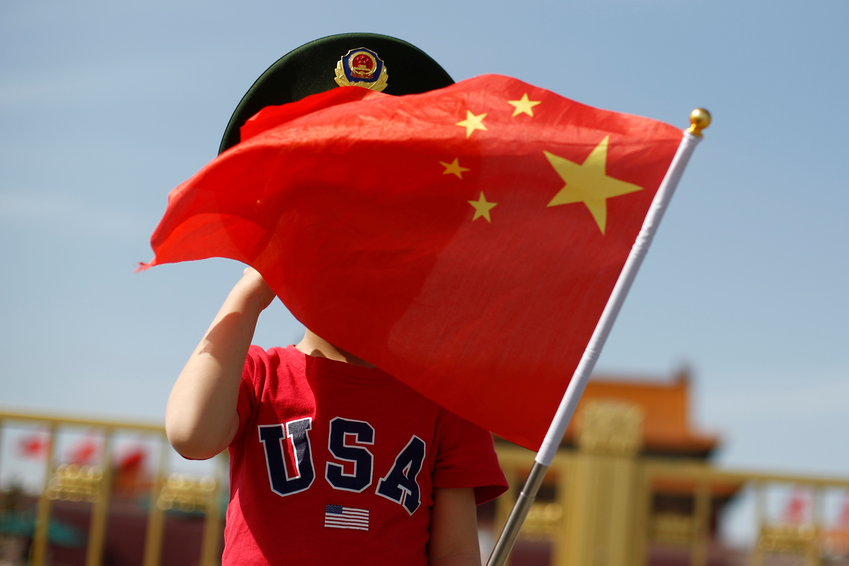 A boy wearing an U.S. t-shirt waves a Chinese national flag in Tiananmen Square in Beijing