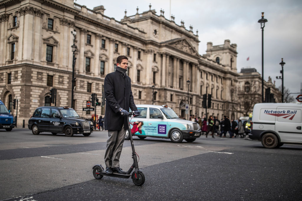A man rides an e-scooter past Parliament Square in London, England earlier this year.