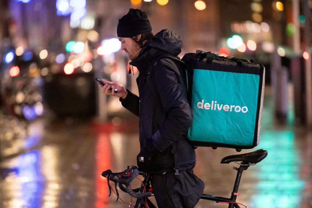 Deliveroo rider checks his phone
