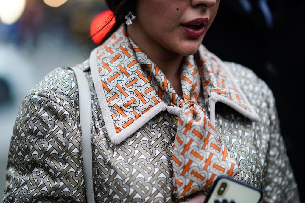 A guest wears a Burberry jacket and monogram scarf, outside Burberry, during London Fashion Week in London in February 2019.