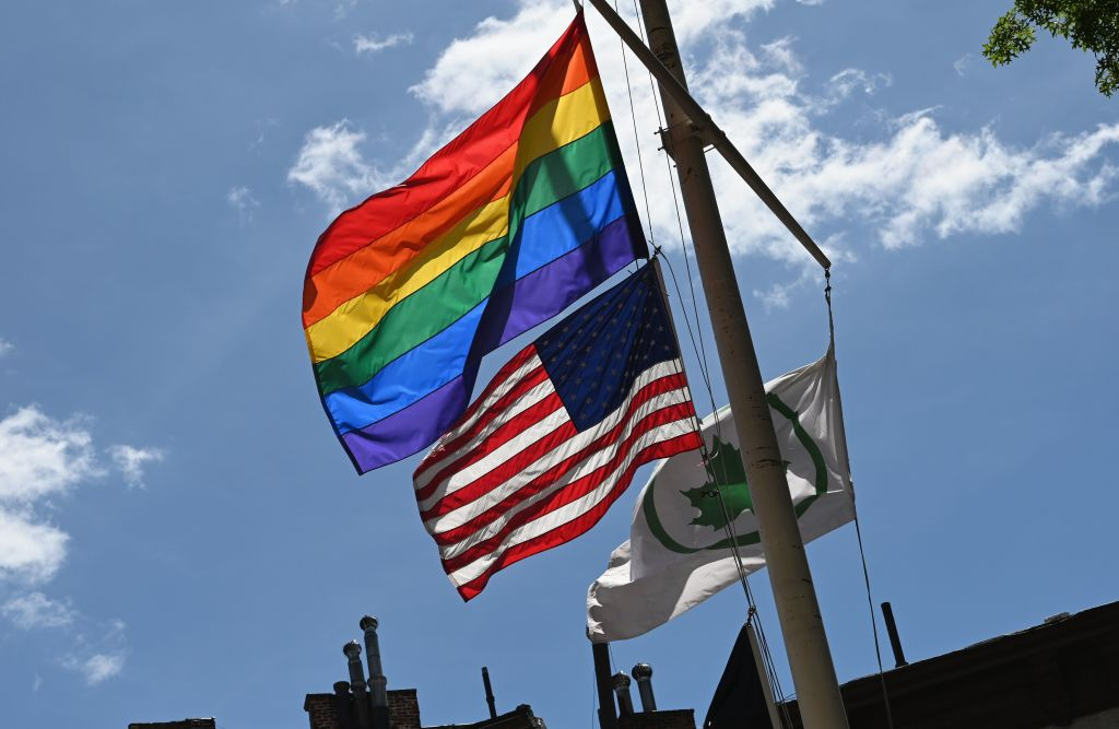 A Rainbow flag and an American flag are seen side by side at the Stonewall National Monument in June