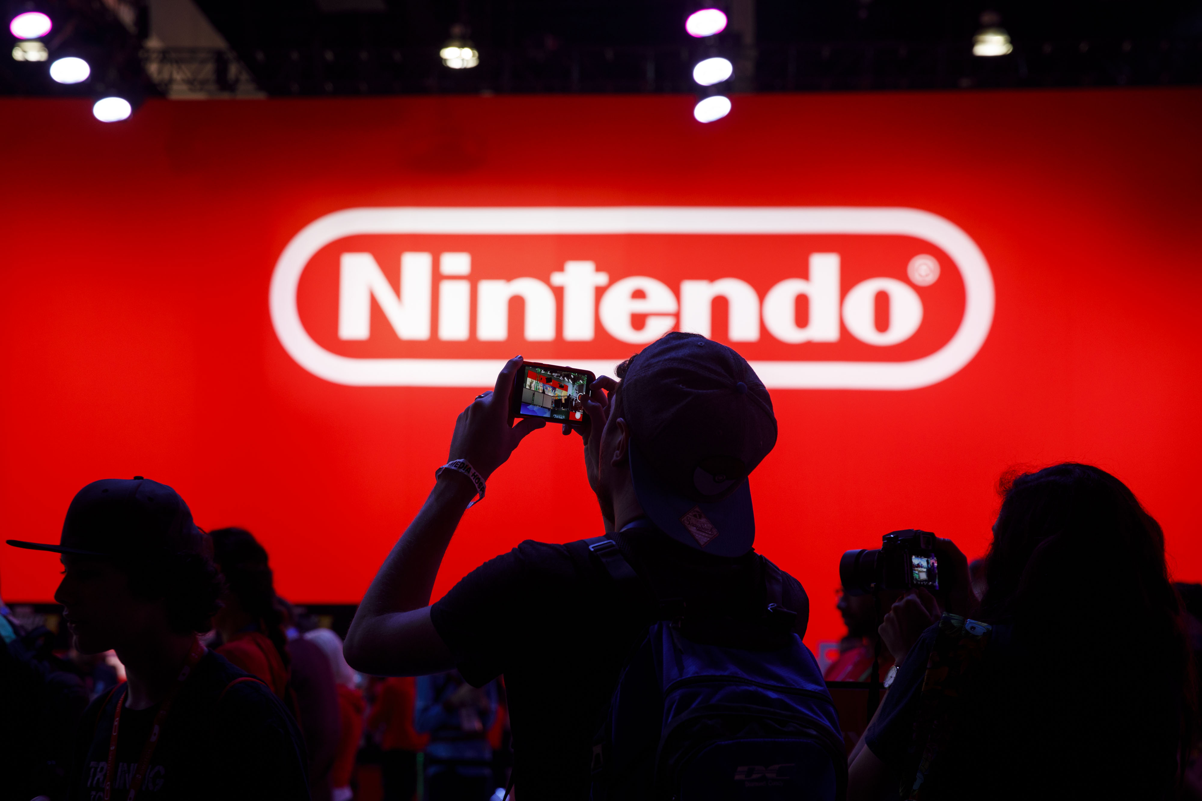 Attendees take photographs while waiting to enter the Nintendo Co. Pokemon Sword and Shield display during the E3 Electronic Entertainment Expo in Los Angeles, California, U.S., on Wednesday, June 12, 2019. For three days, leading-edge companies, groundbreaking new technologies and never-before-seen products are showcased at E3. Photographer: