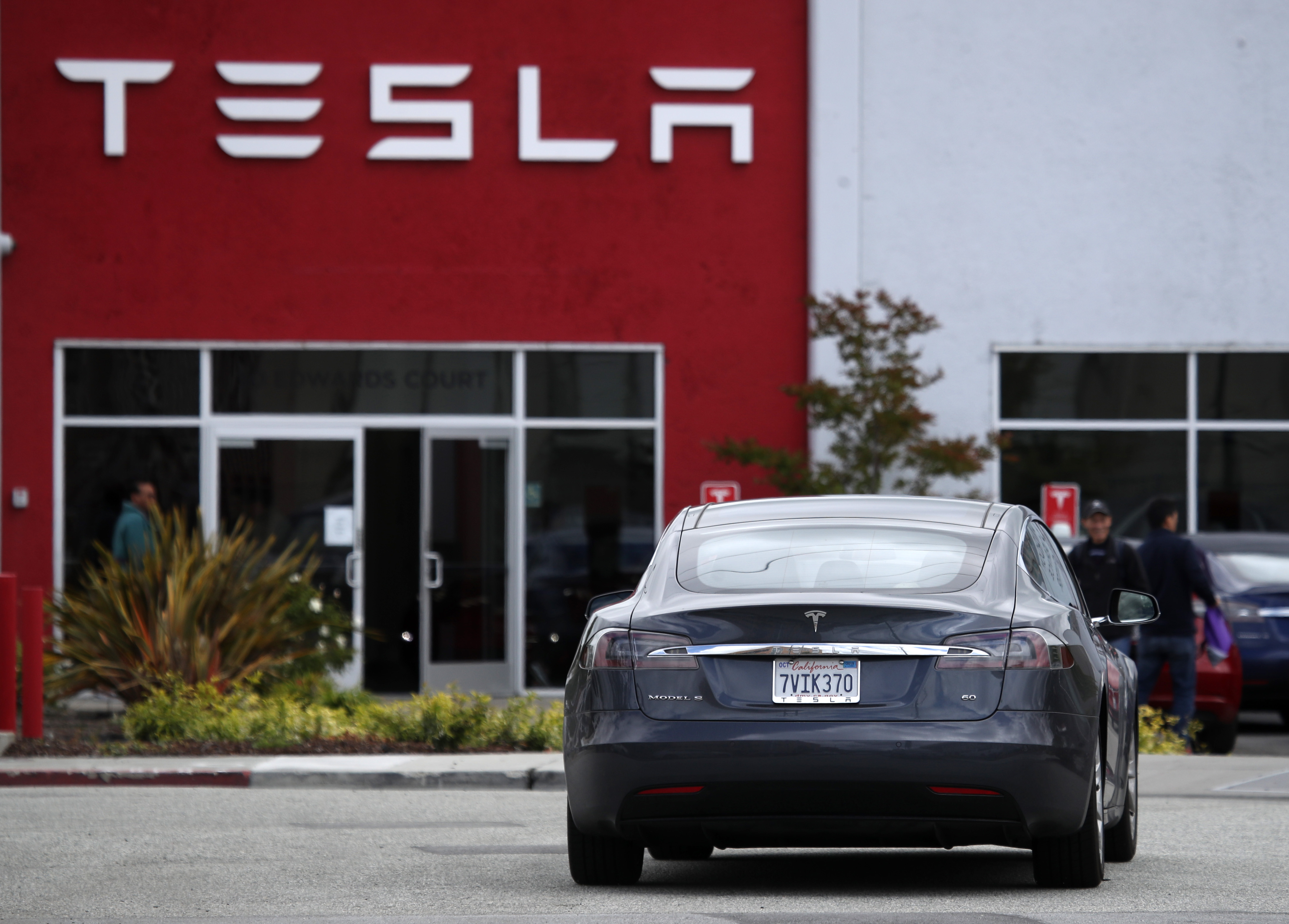 A Tesla Model S drives into the parking lot of a Tesla showroom and service center. (Photo by Justin Sullivan/Getty Images)