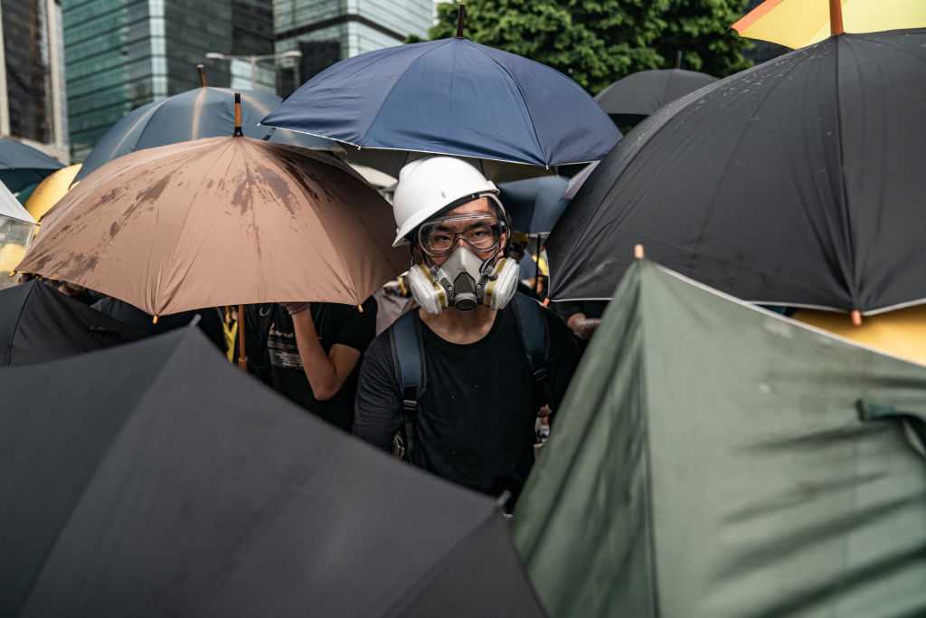 Anti-extradition protesters use umbrellas to defend themselves during a clash with police outside the Legislative Council Complex ahead of the annual flag raising ceremony of 22nd anniversary of the city's handover from Britain to China on July 1, 2019 in Hong Kong, China. (Photo by Anthony Kwan/Getty Images)