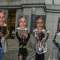 Four young women hold up signs with Jeffrey Epstein's mugshot on them.