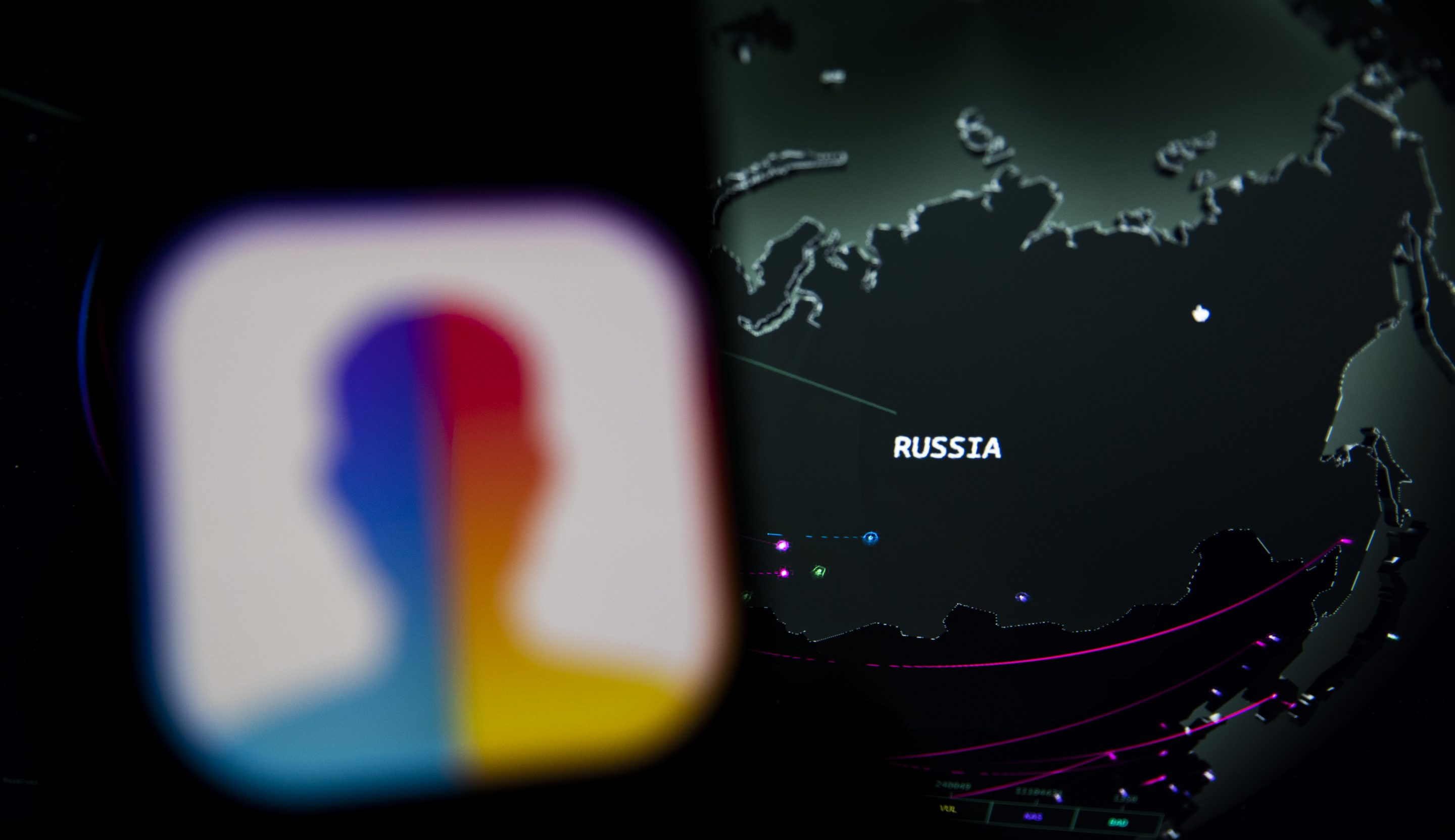 "FaceApp displayed on the screen of a smartphone and in background a cybermap of Russia. The popular app is in the in the eye of a political storm in the U.S., with one senator urging an FBI investigation into its ""national security and privacy risks.""  (Photo illustration by Manuel Romano/NurPhoto via Getty Images)"