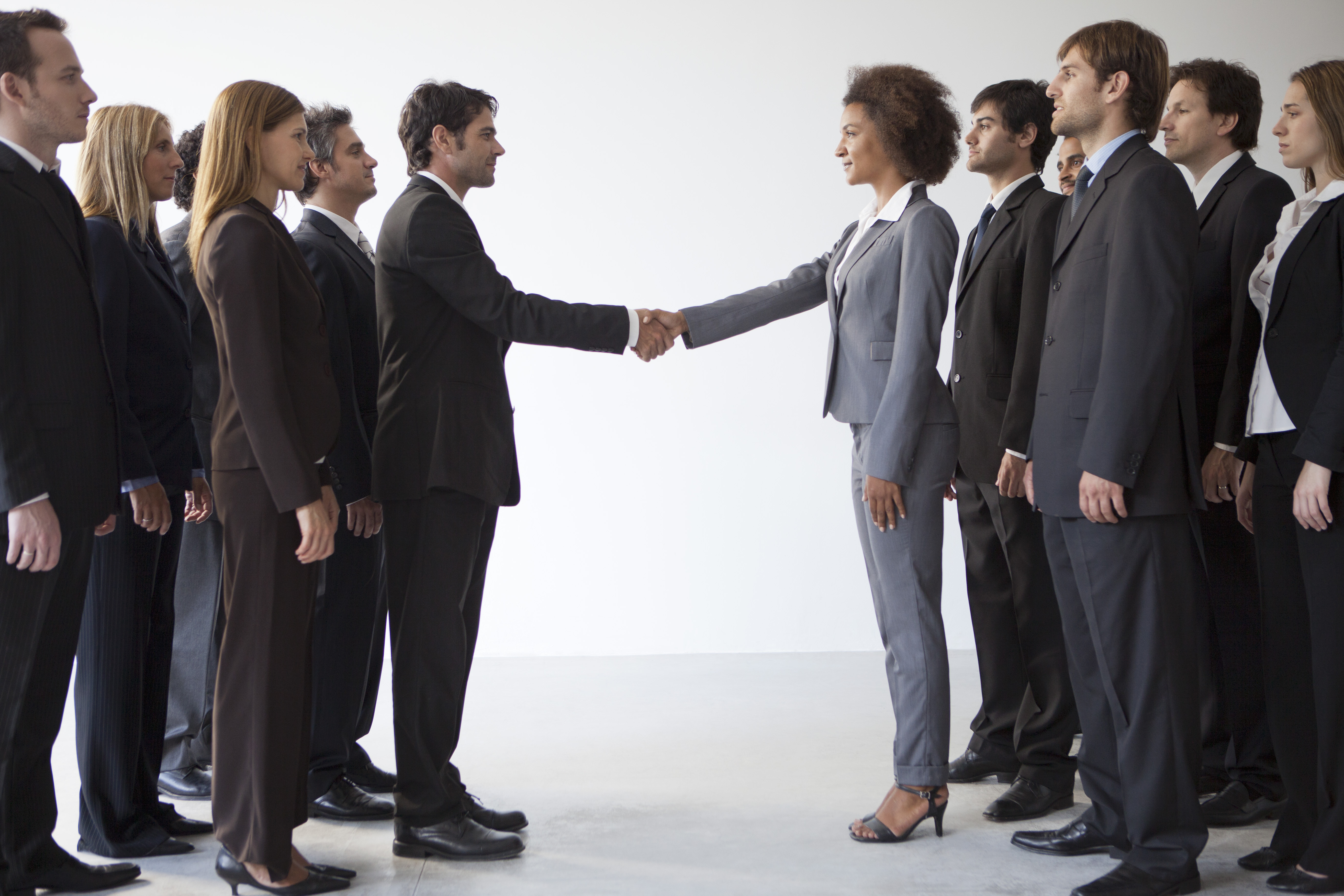 two groups of people shake hands