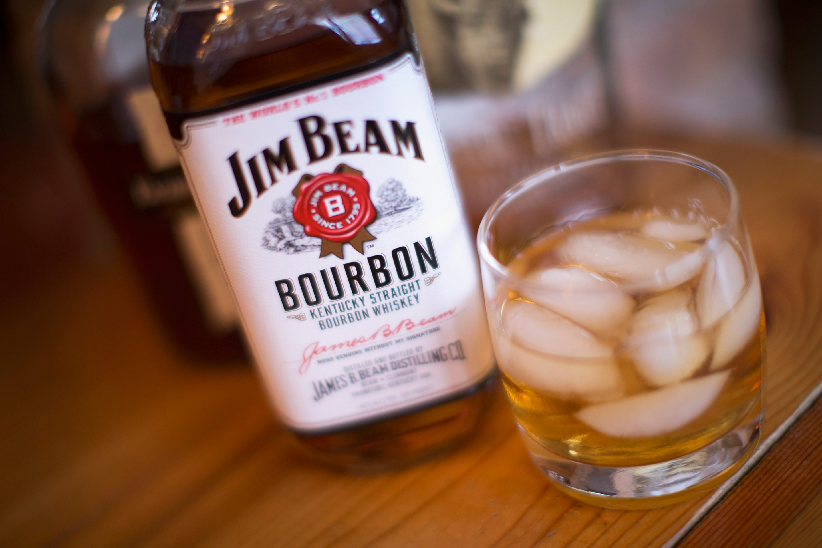 A bottle of Jim Beam bourbon sitting next to a glass of bourbon on the rocks