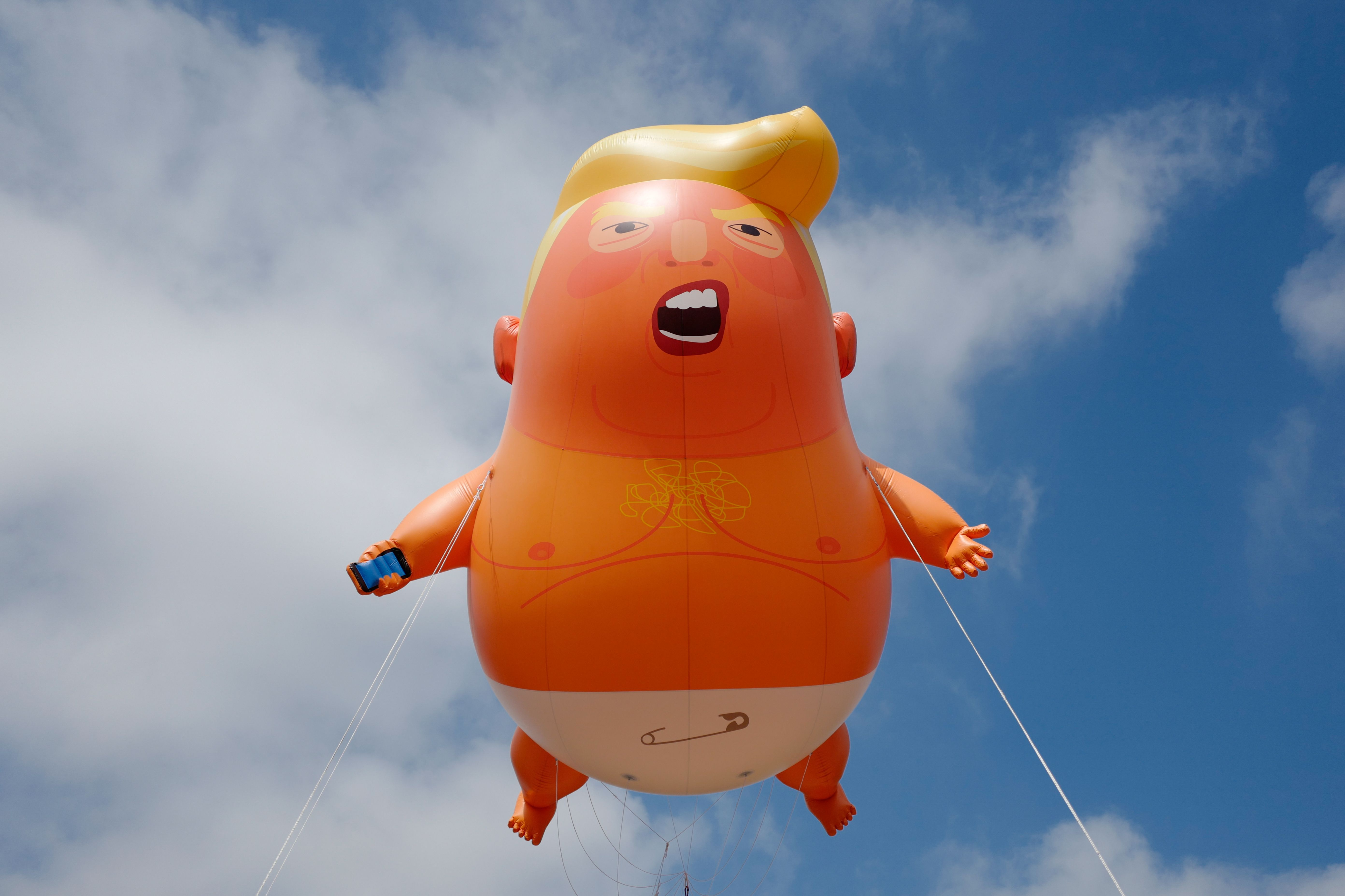 "A giant balloon inflated by activists depicting US President Donald Trump as an orange baby is seen during a demonstration against Trump's visit to the UK in Parliament Square in London on July 13, 2018. - US President Donald Trump launched an extraordinary attack on Prime Minister Theresa May's Brexit strategy, plunging the transatlantic ""special relationship"" to a new low as they prepared to meet Friday on the second day of his tumultuous trip to Britain."