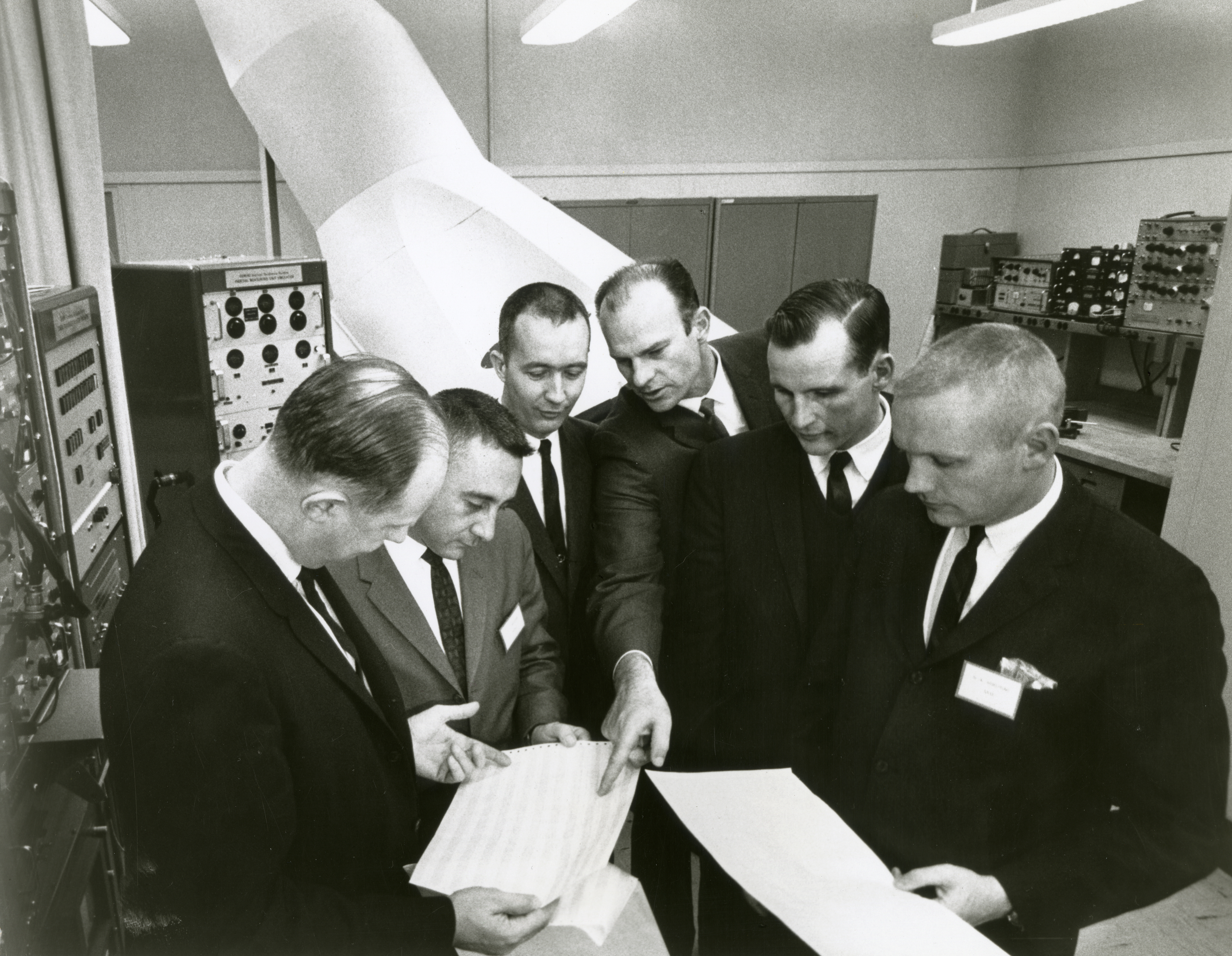 At IBM in Owego, N.Y., astronauts review printed logs of a simulated descent into earth's atmosphere. Tests at Owego used a Gemini spacecraft mockup, in background, and an IBM 7090 programmed to act like an on-board computer. Two years later, Astronaut Neil Armstrong (right) used IBM's Gemini computer to steer Gemini 8 to a safe landing in the Pacific. From left: Arthur Cooper, a leader of IBM's space program; astronaut Virgil (Gus) Grissom; astronaut James McDivitt; C.D. Babb of IBM avionics; astronaut Edward White; and astronaut Neil Armstrong.