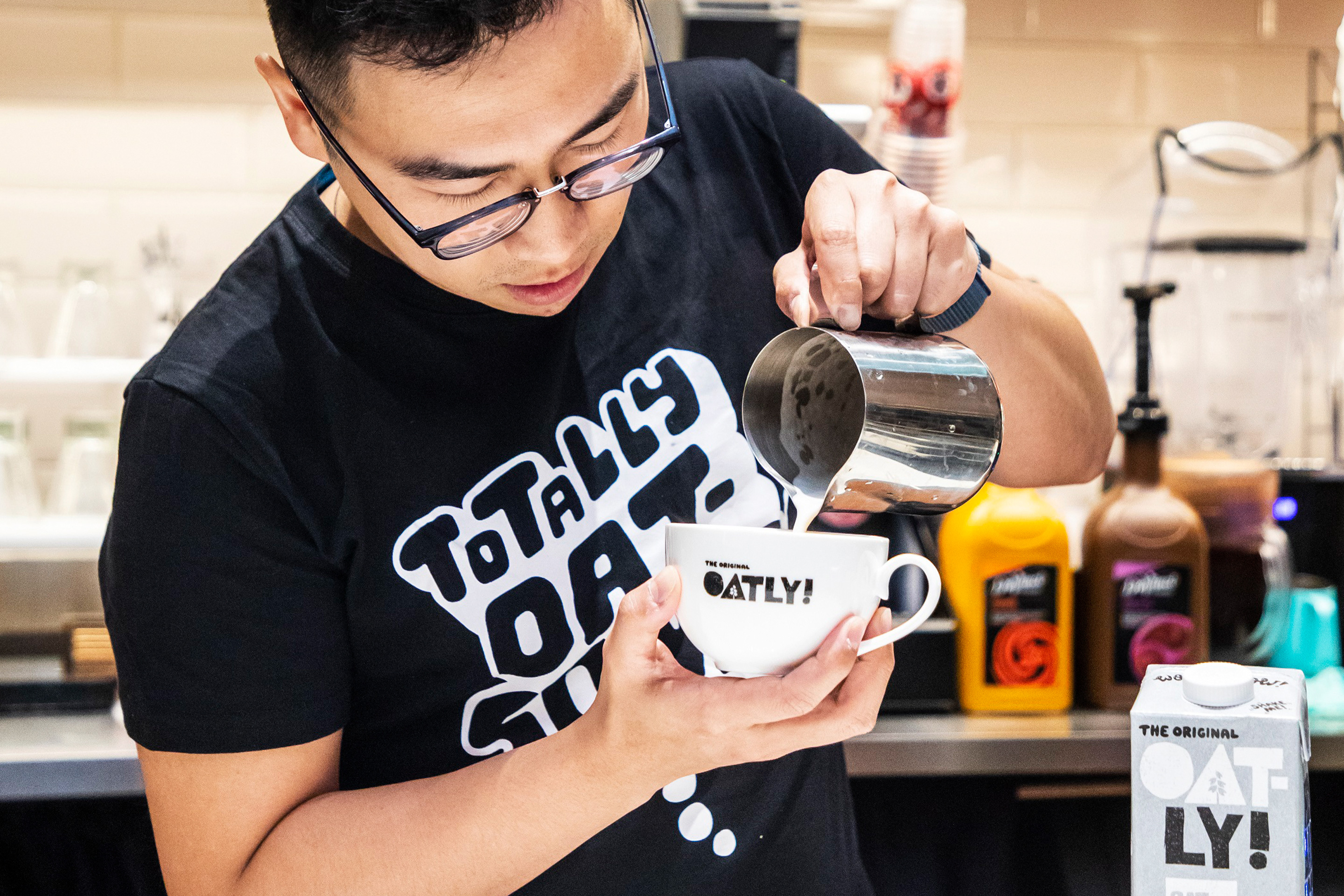 A barista in a Hong Kong coffee shop uses Oatly to craft latte foam. Photo: Courtesy of Oatly