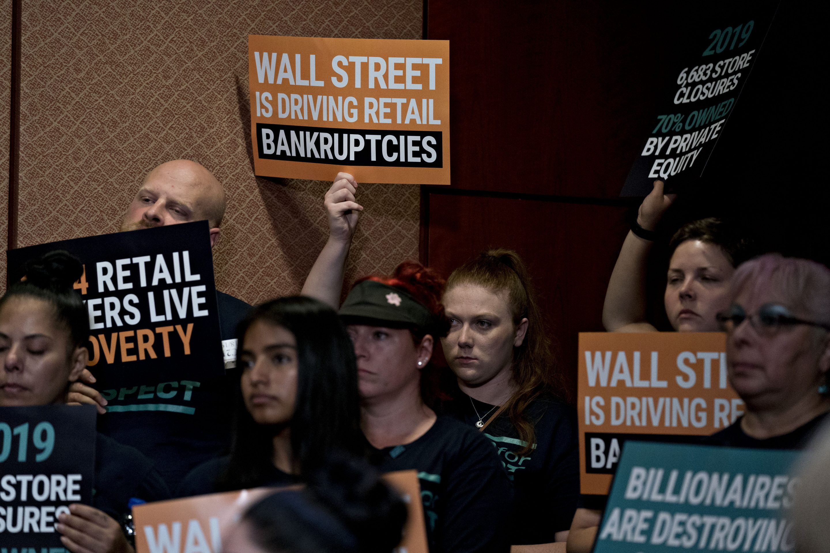 An attendee holds up a sign during a news conference on the Stop Wall Street Looting Act on Capitol Hill in Washington, D.C., on Thursday, July 18, 2019.