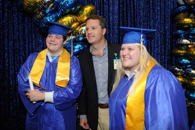 Walmart CEO Doug McMillon poses with two recent Academy graduates.