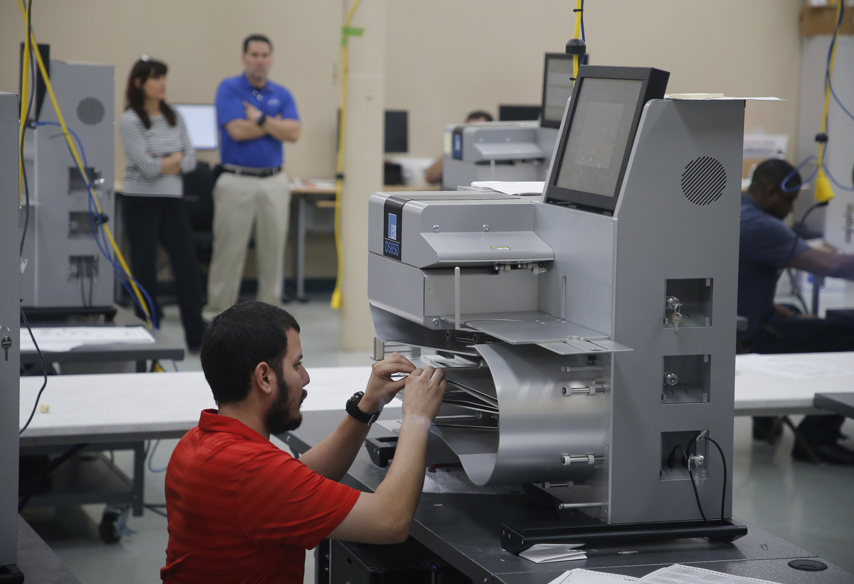 LAUDERHILL, FL - NOVEMBER 11: An elections official works on a counting machine as it was calibrated prior to the start of a recount of all votes at the Broward County Supervisor of Elections Office on November 11, 2018 in Lauderhill, Florida. Voting machines and counting systems made by Election Systems & Software were improperly configured and ripe for election hacking, Vice reports. (Photo by Joe Skipper/Getty Images)