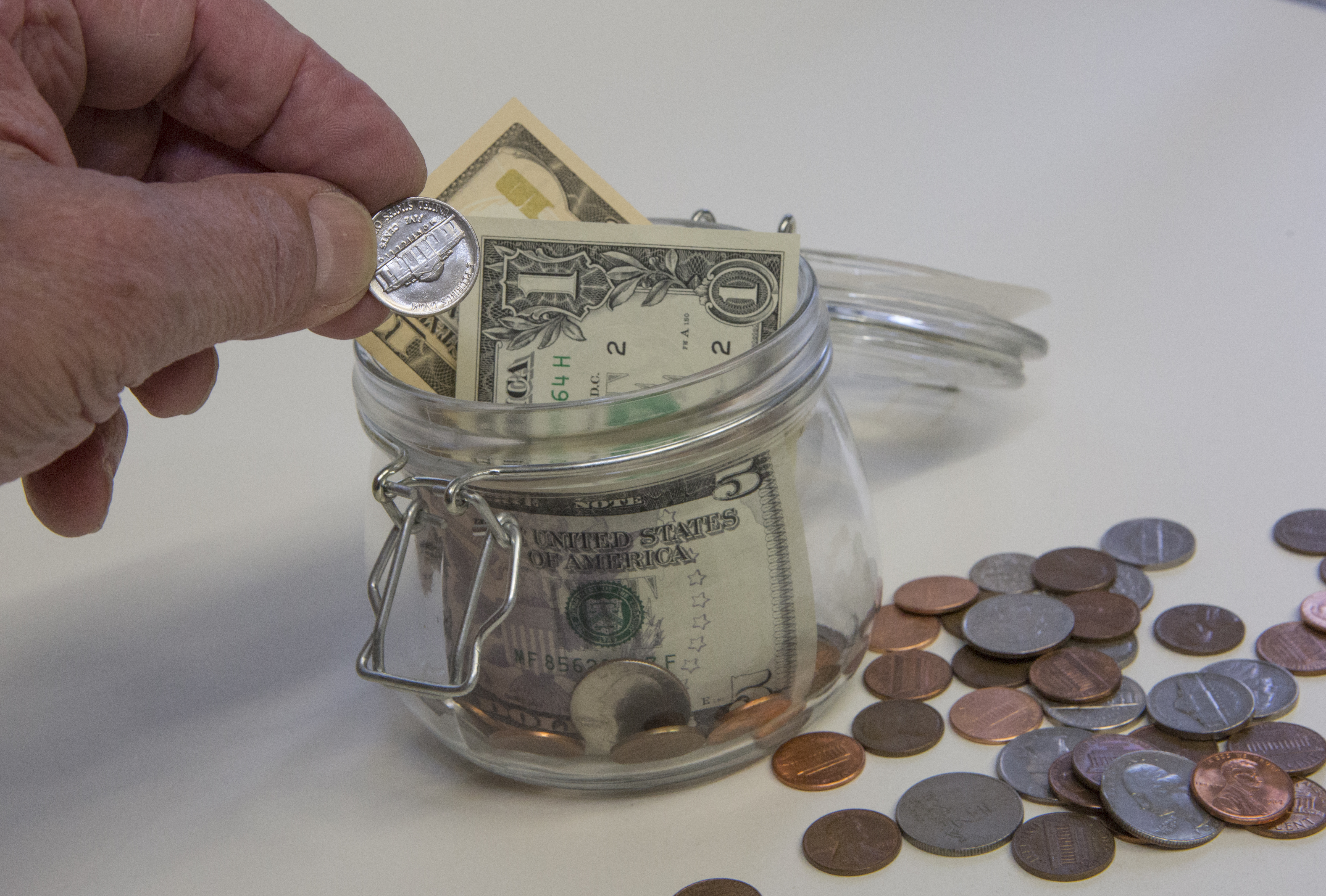 A hand drops a nickel into a savings jar
