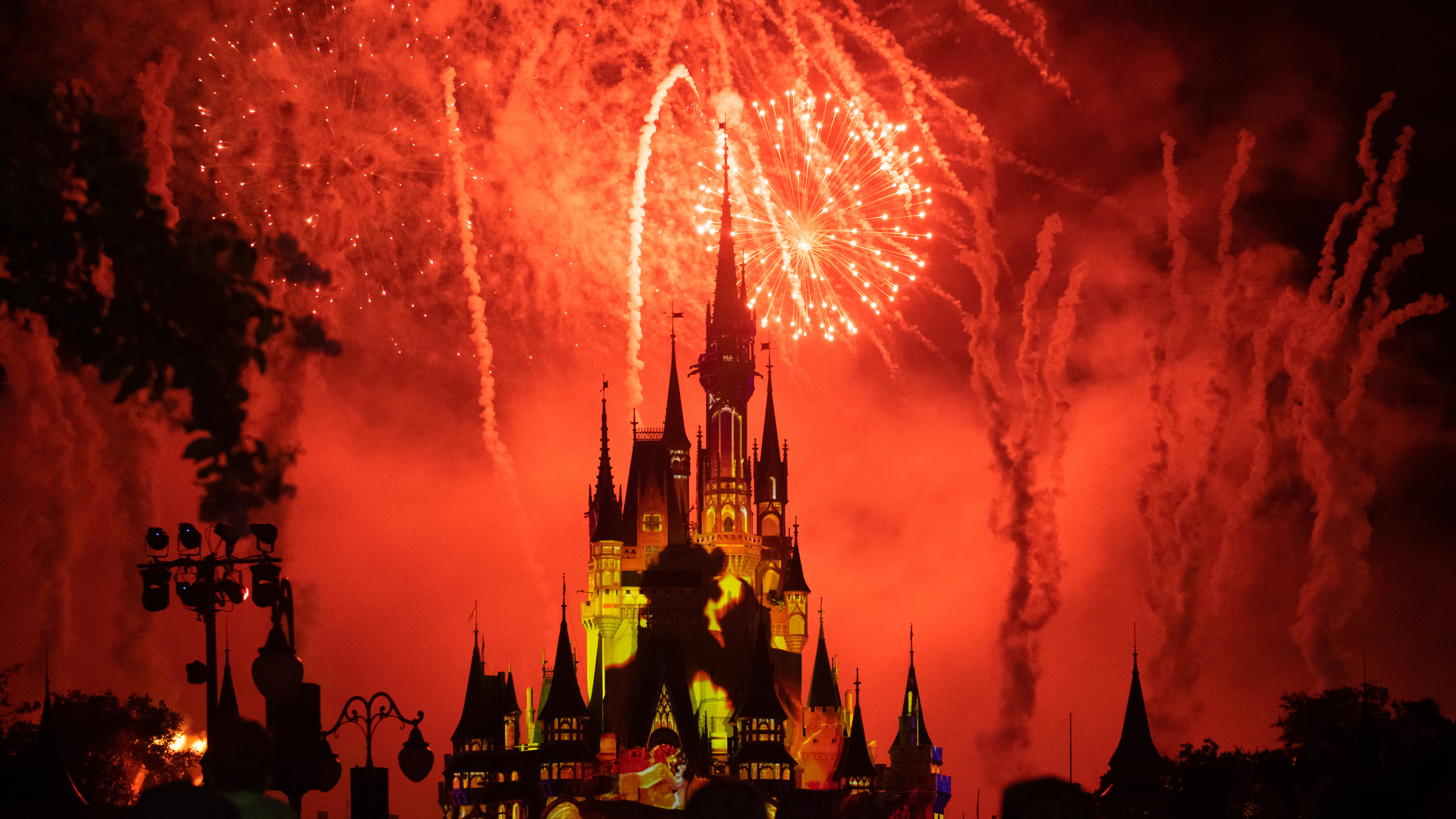 Red fireworks and yellow strobe lights illuminating the Cinderella Castle in the Walt Disney's Magic Kingdom themed park.