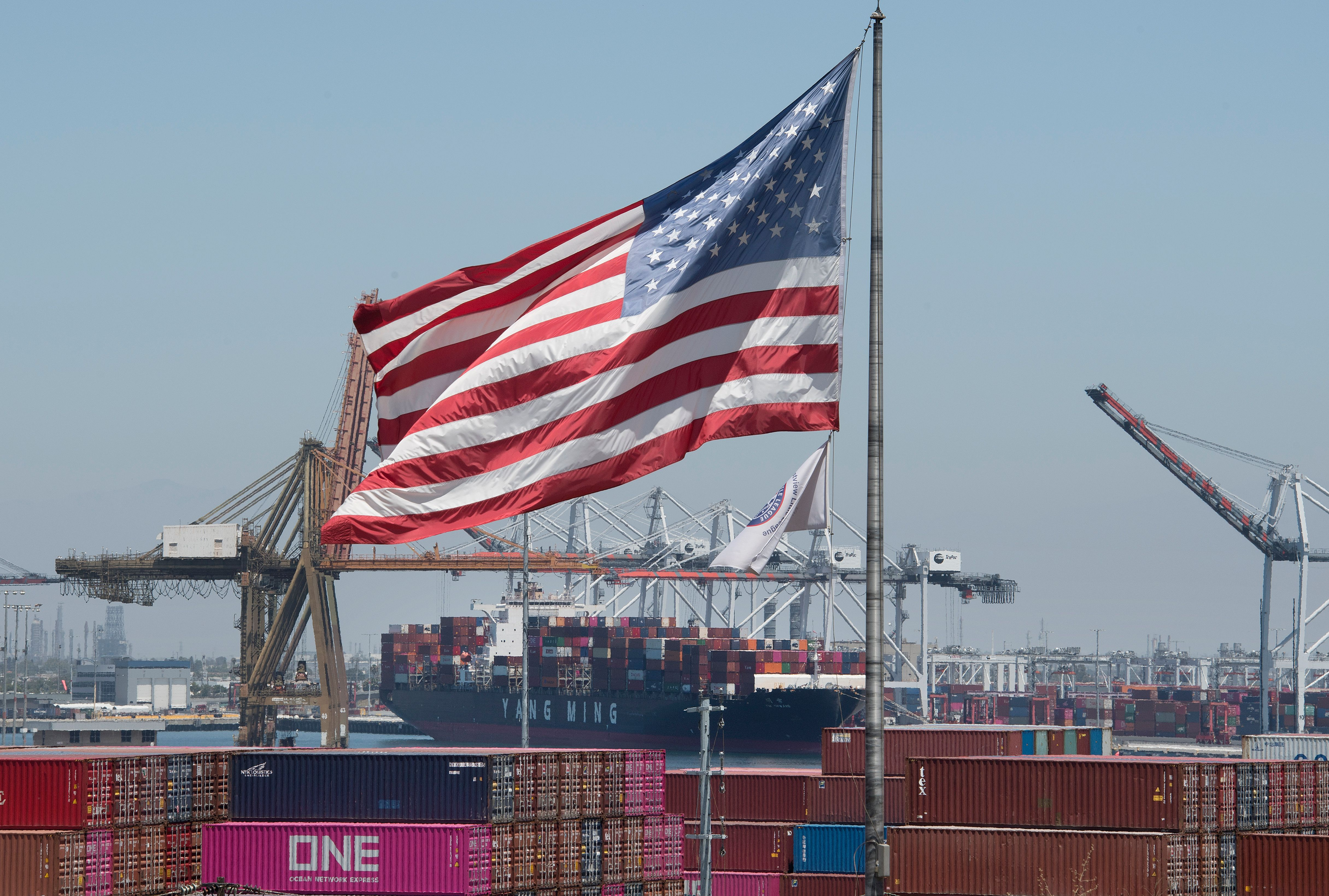 The US flag flies over a container ship unloading it's cargo from Asia, at the Port of Long Beach, California on August 1, 2019.