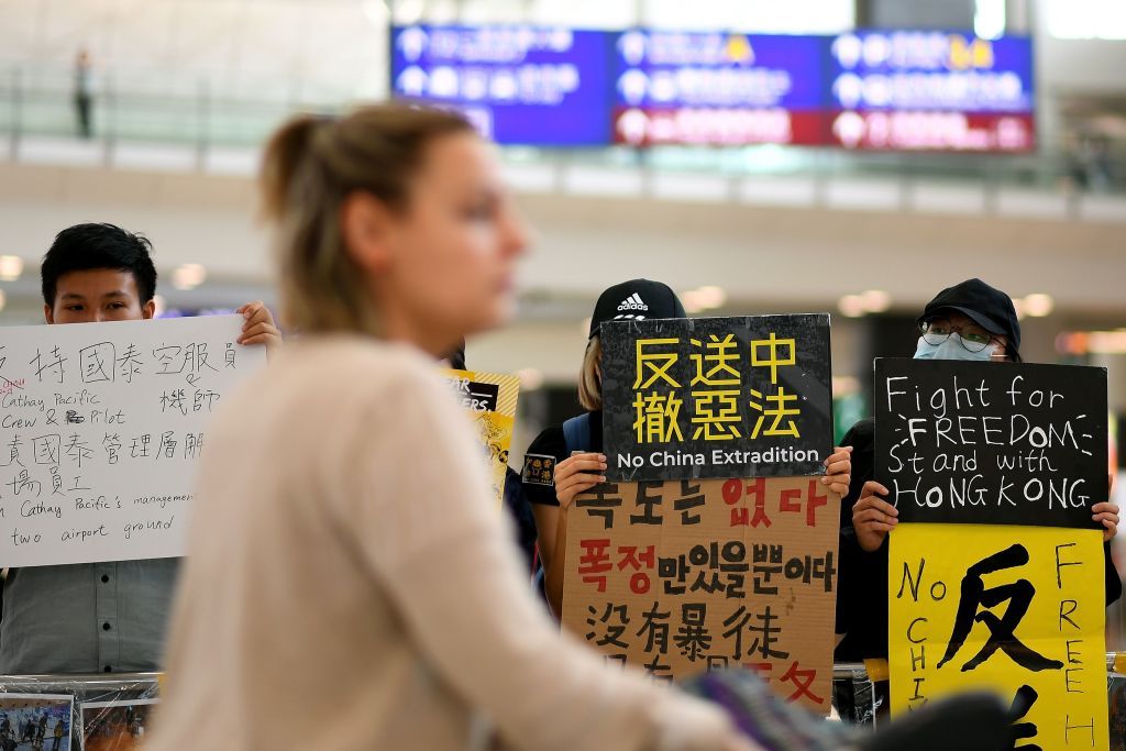 Hong Kong protestors hold signs at airport