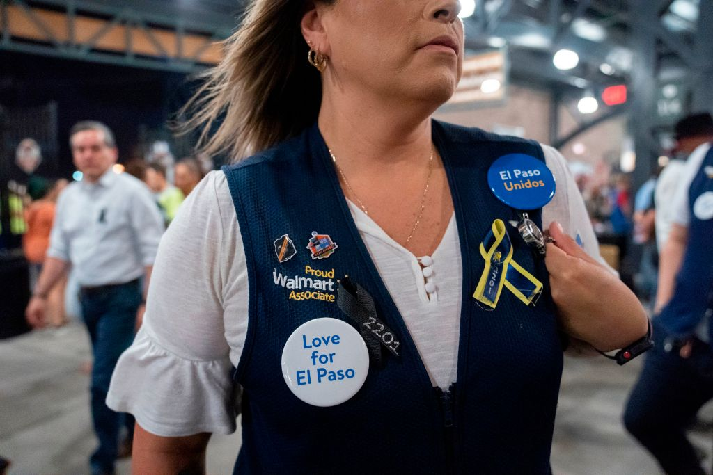 A Walmart employee attends a community memorial service for the 22 victims of the mass shooting at an El Paso Walmart, on Aug. 14.