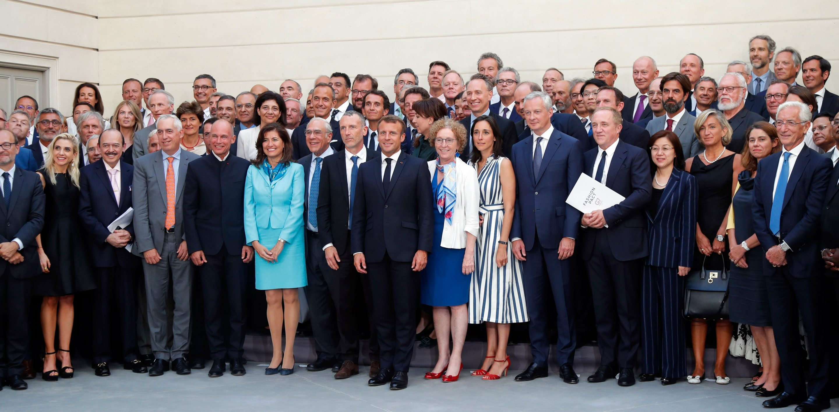 French President Emmanuel Macron, center, poses with G7-Summit civil society representatives, including Kering chairman and CEO François-Henri Pinault, right, holding the G7 Fashion Pact.
