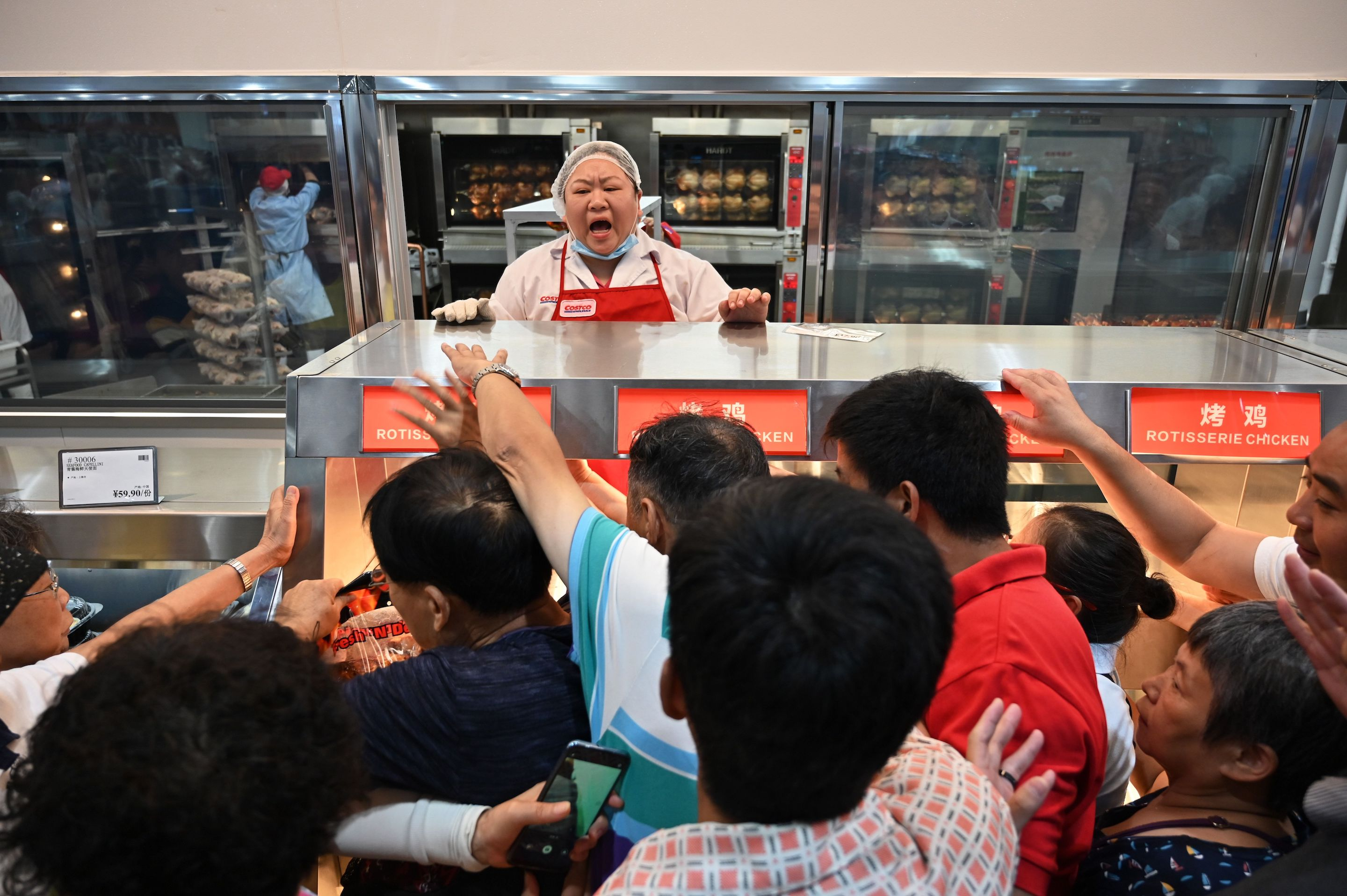 Shanghai customers clamor at the roast chicken counter at Costco's first store in China, which debuted today. Crowds surged through the store.