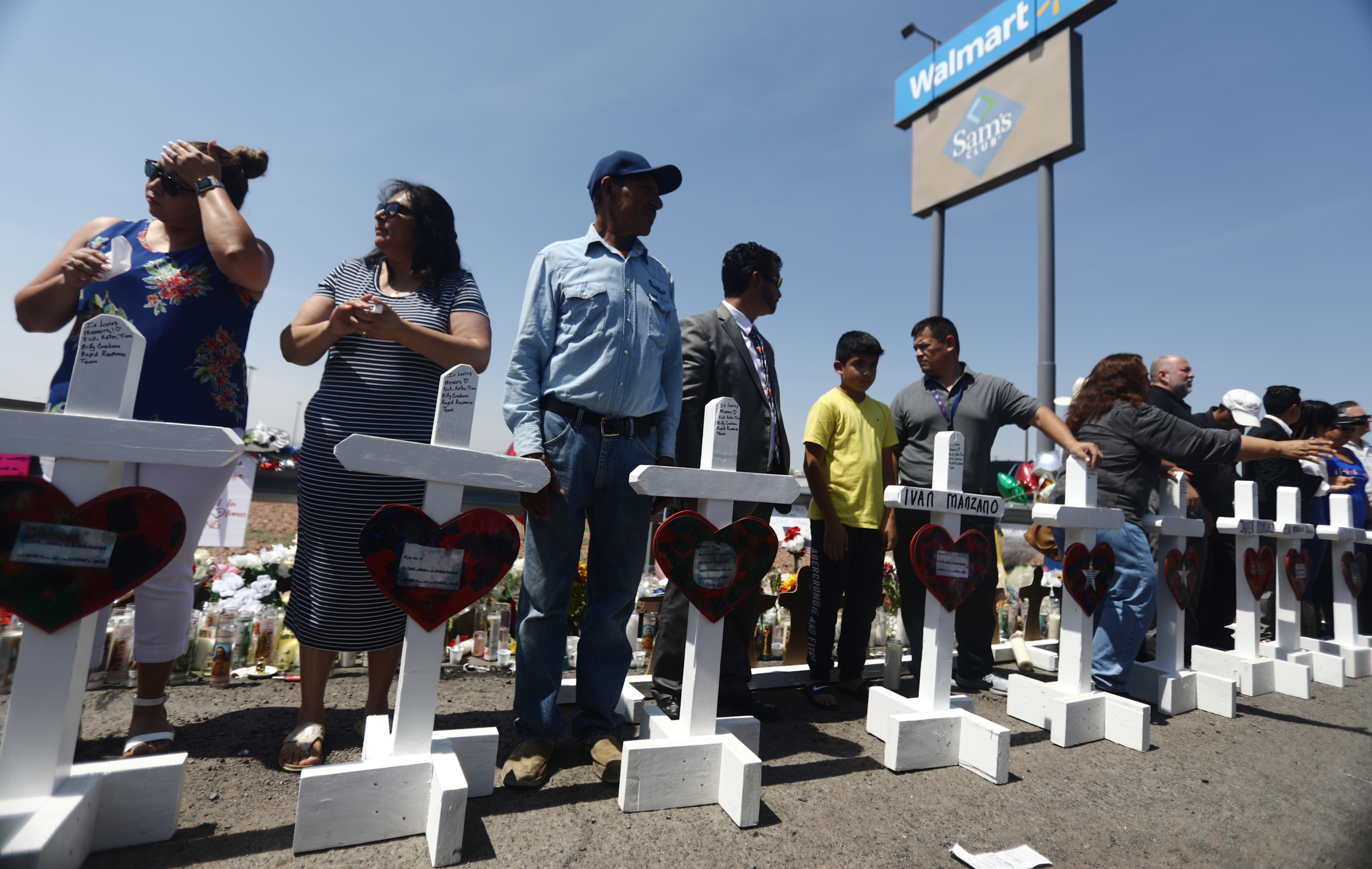 Volunteers stand with handmade crosses memorializing the victims of a mass shooting in El Paso.