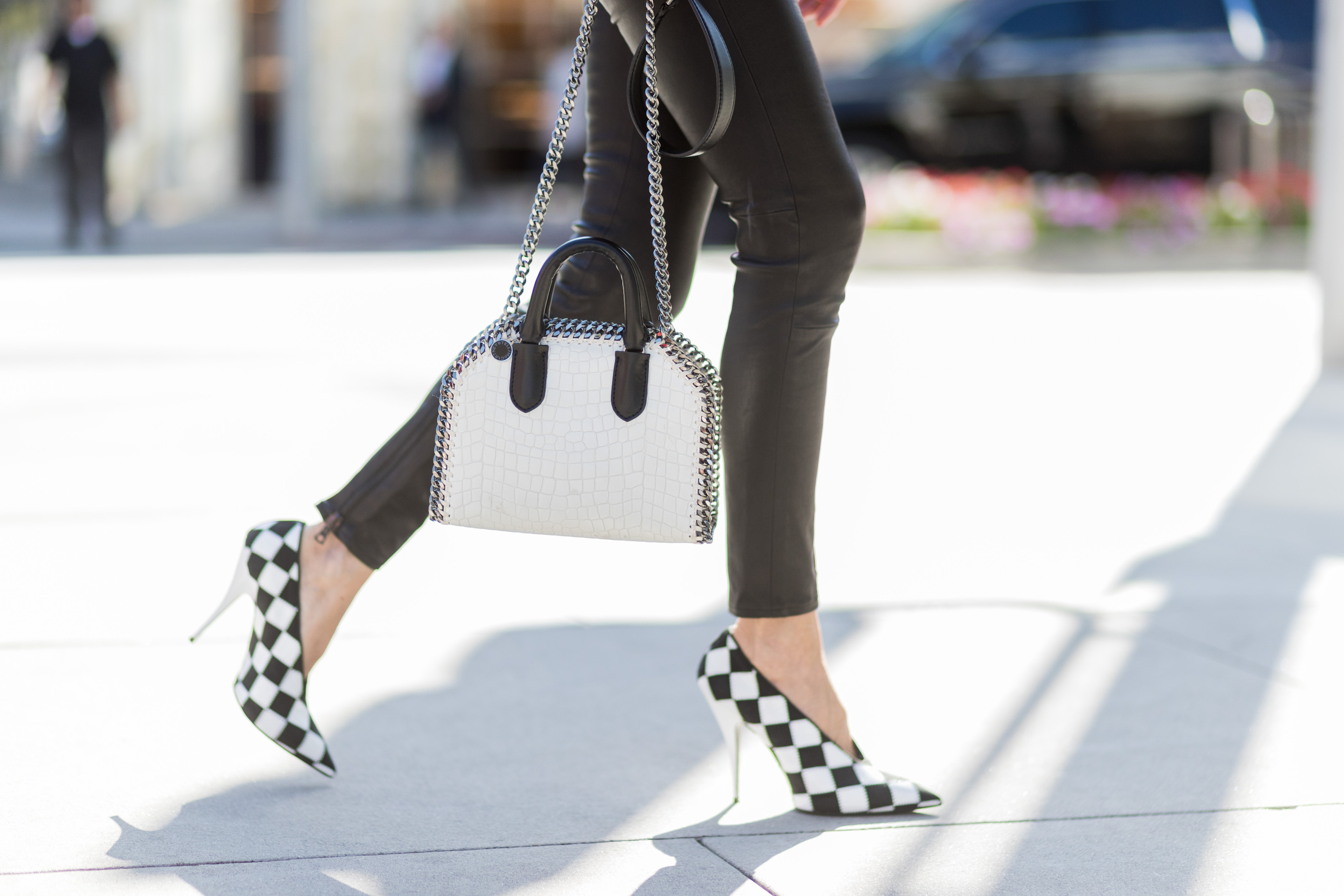 Faux leather is increasingly represented in fashion, and is sometimes mixed with the real thing. This model is wearing skinny leather pants by Unravel, paired with black and white vegan patent Stella McCartney check pointed-toe pumps, and is carrying a Falabella Box mini faux-leather cross-body bag.