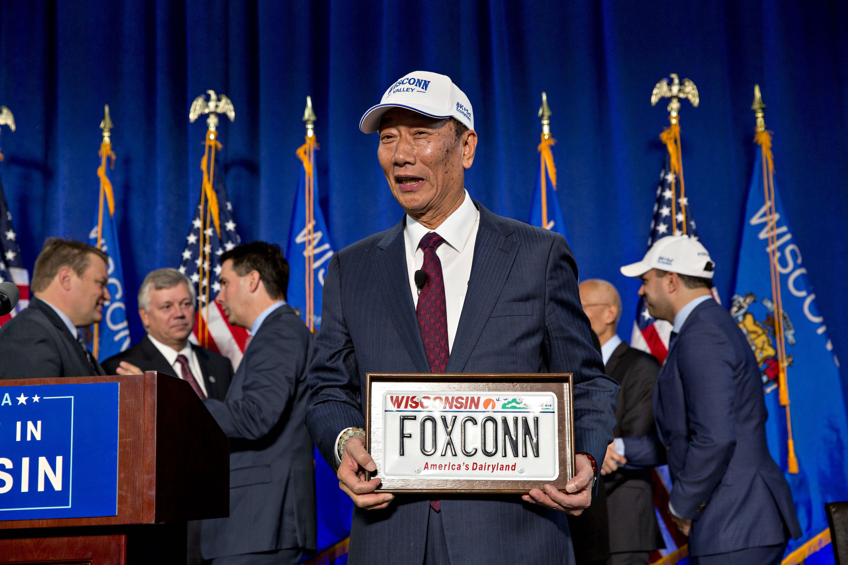 "Billionaire Terry Gou, chairman of Foxconn Technology Group, holds a ""FOXCONN"" Wisconsin license plate during an event in Racine, Wisconsin, U.S., on Friday, Nov. 10, 2017. The agreement grants the electronics giant $3 billion in tax incentives for a massive manufacturing campus in southeastern Wisconsin. Photographer: Daniel Acker/Bloomberg"