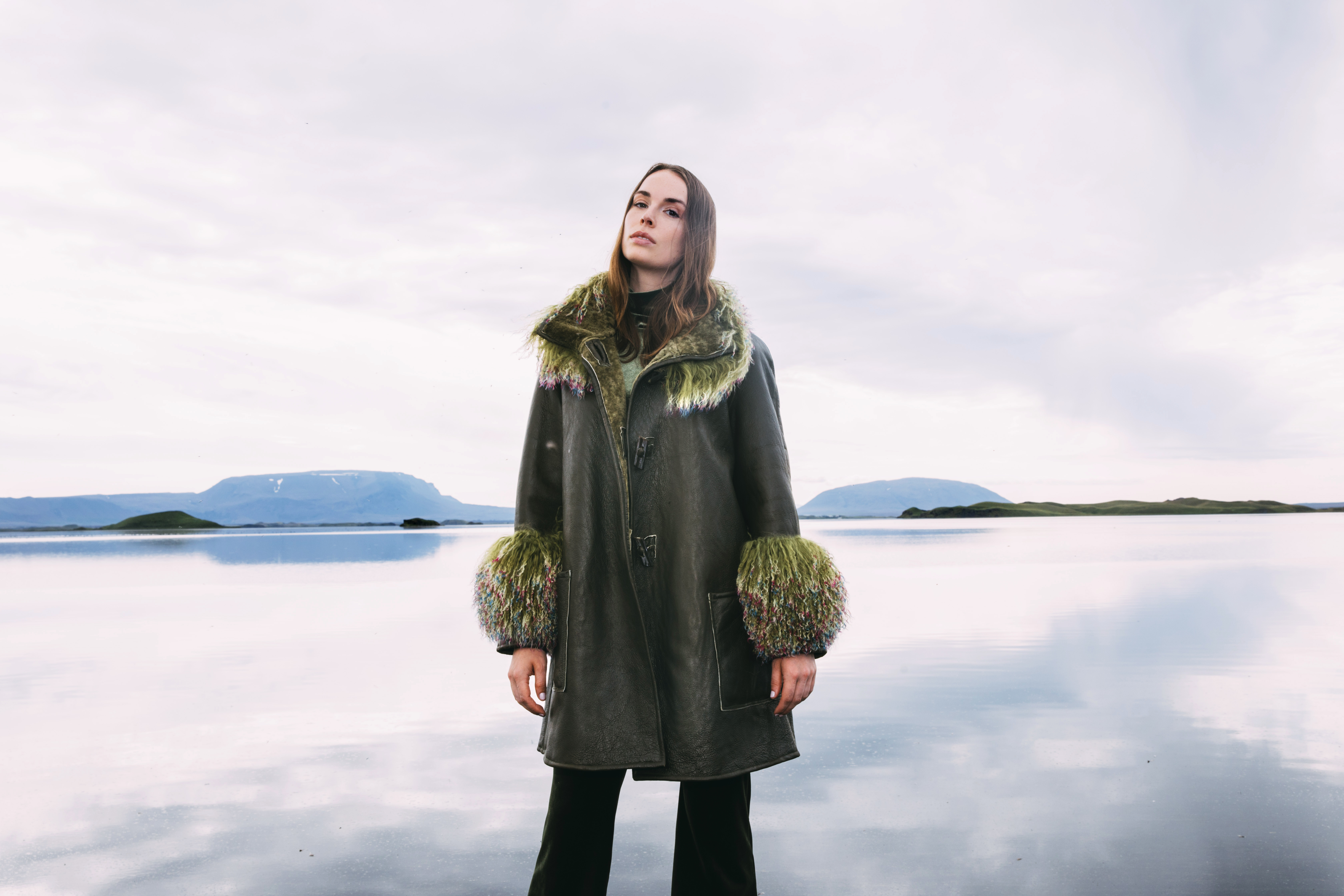 Therma Kōta cofounder and creative director Sophie Lundström Halbert models the label's Olavia reversible shearling in moss.
