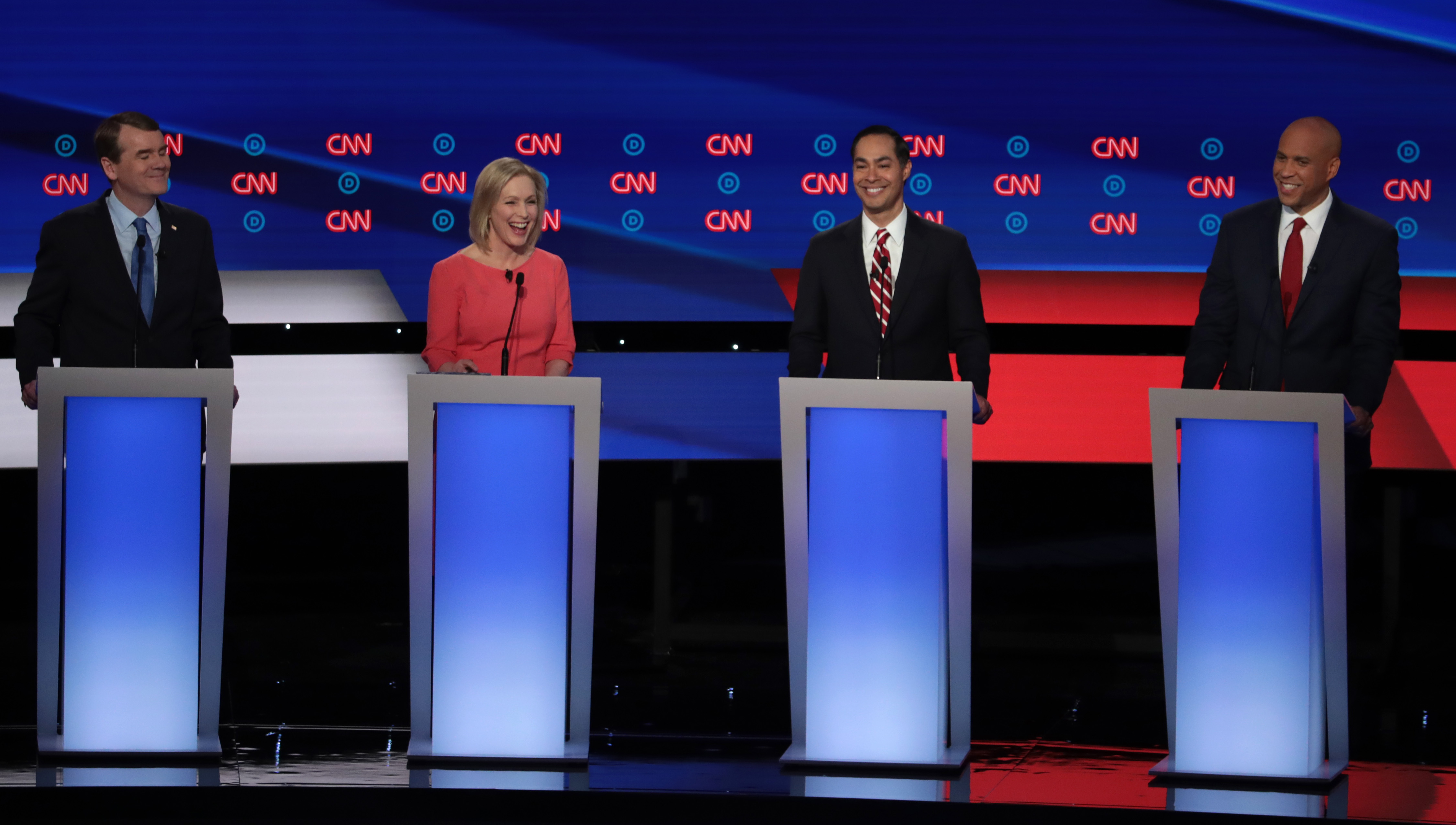 Democratic presidential candidates Sen. Michael Bennet (D-CO) (L-R), Sen. Kirsten Gillibrand (D-NY), former housing secretary Julian Castro, and Sen. Cory Booker (D-NJ) smile during the Democratic Presidential Debate at the Fox Theatre July 31, 2019 in Detroit, Michigan.