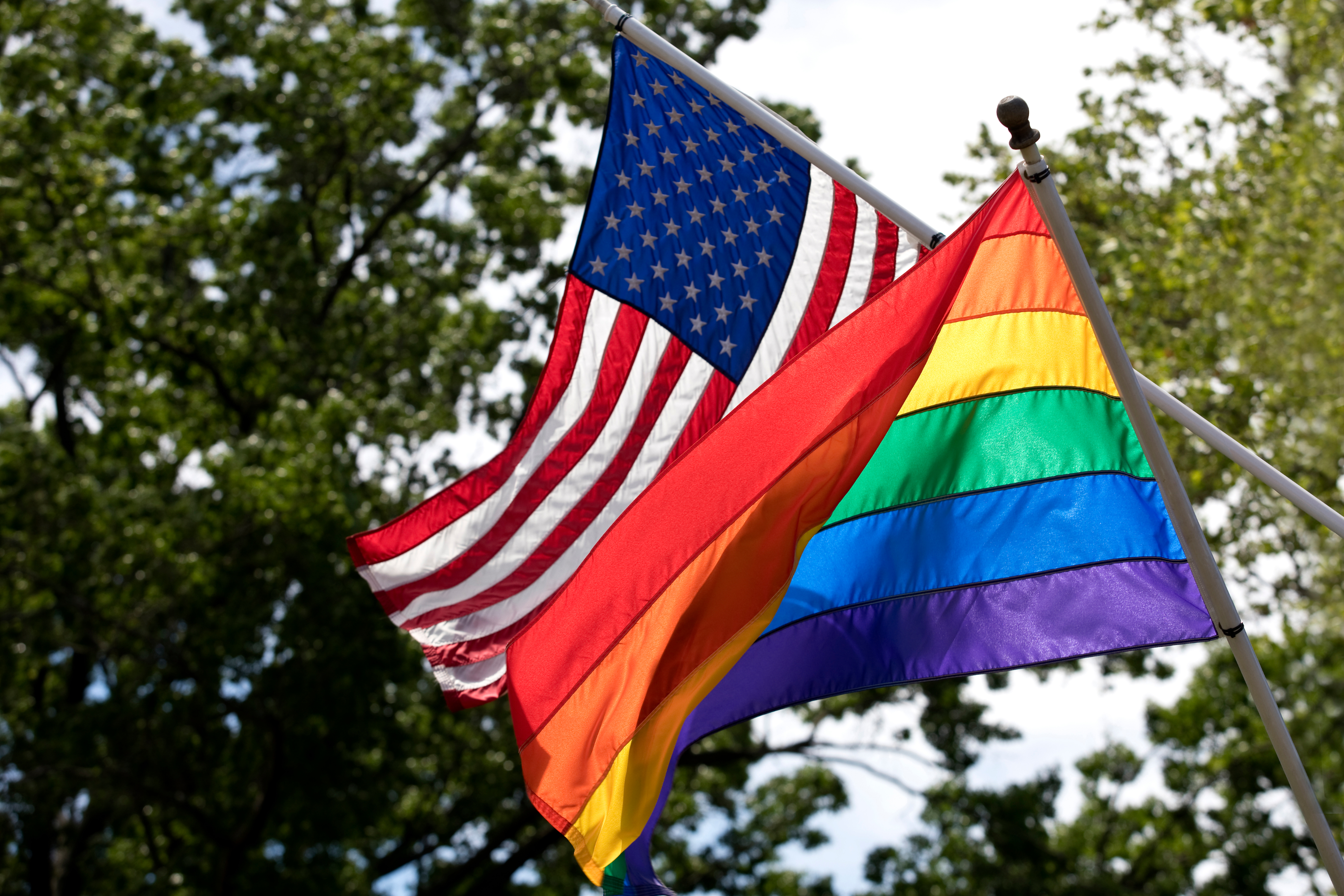 The rainbow pride and American flags fly in the wind together.