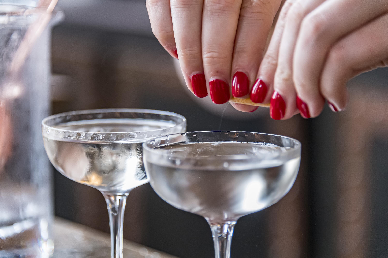 A bartender prepares a vodka martini.