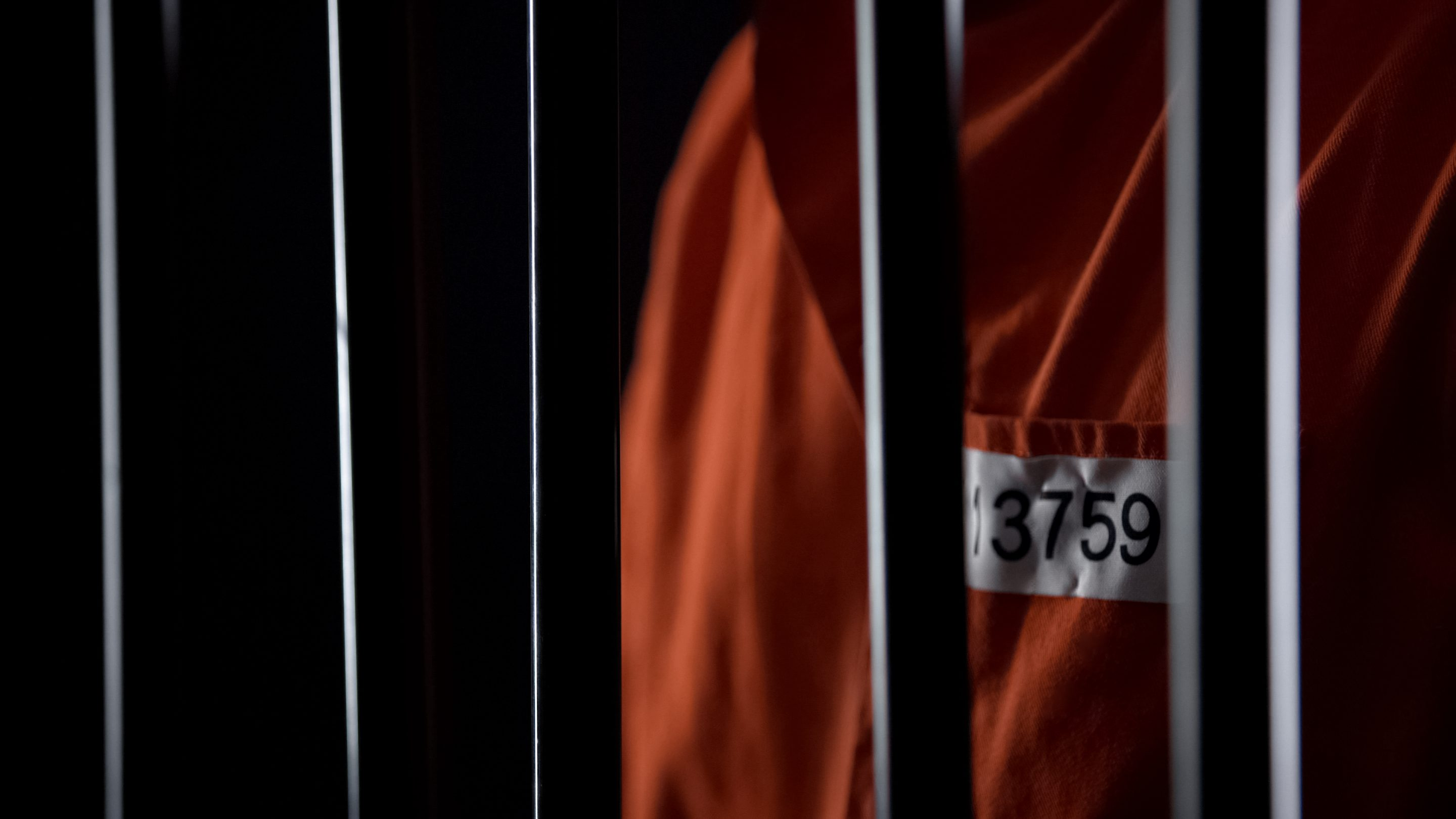 Prisoner in orange uniform standing behind bars